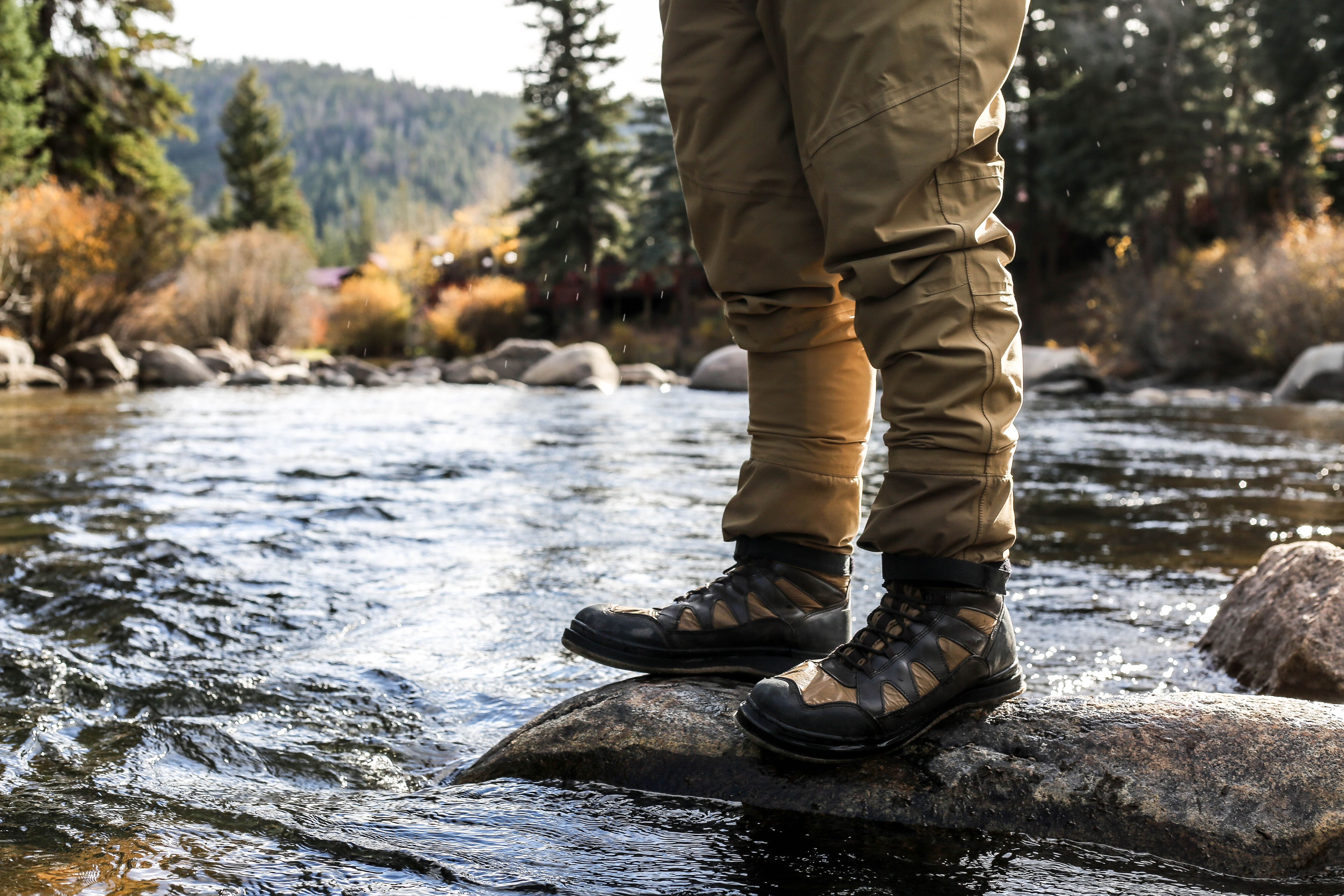 Low shot of a hiker's boots standing on a rock in a stream