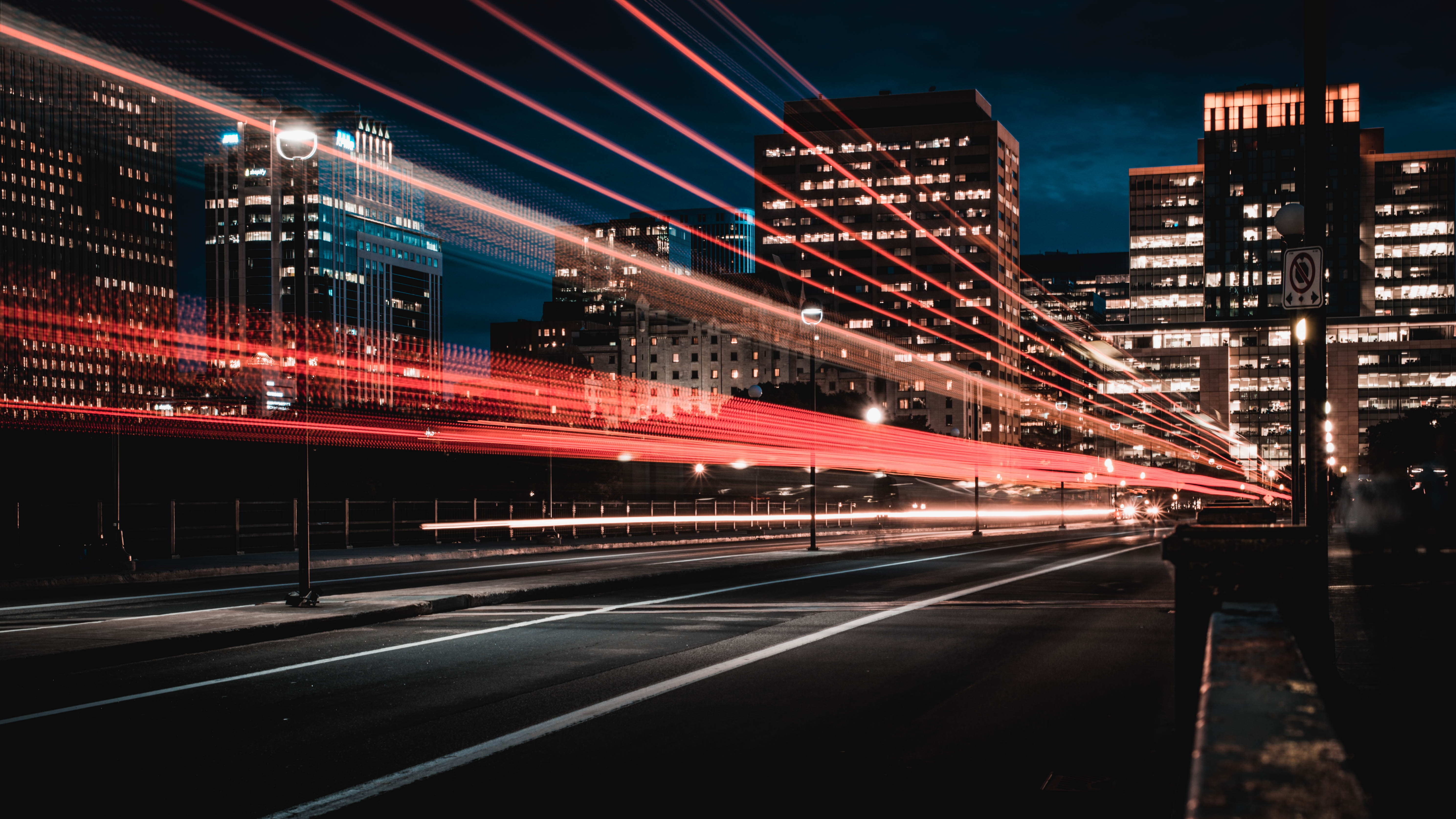 A long-exposure shot of a road in Ottawa with red light trails from the passing cars