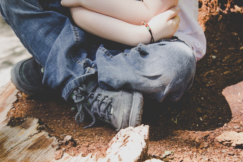 A child in jeans, boots, and a bracelet sits on dirt, crossing their legs