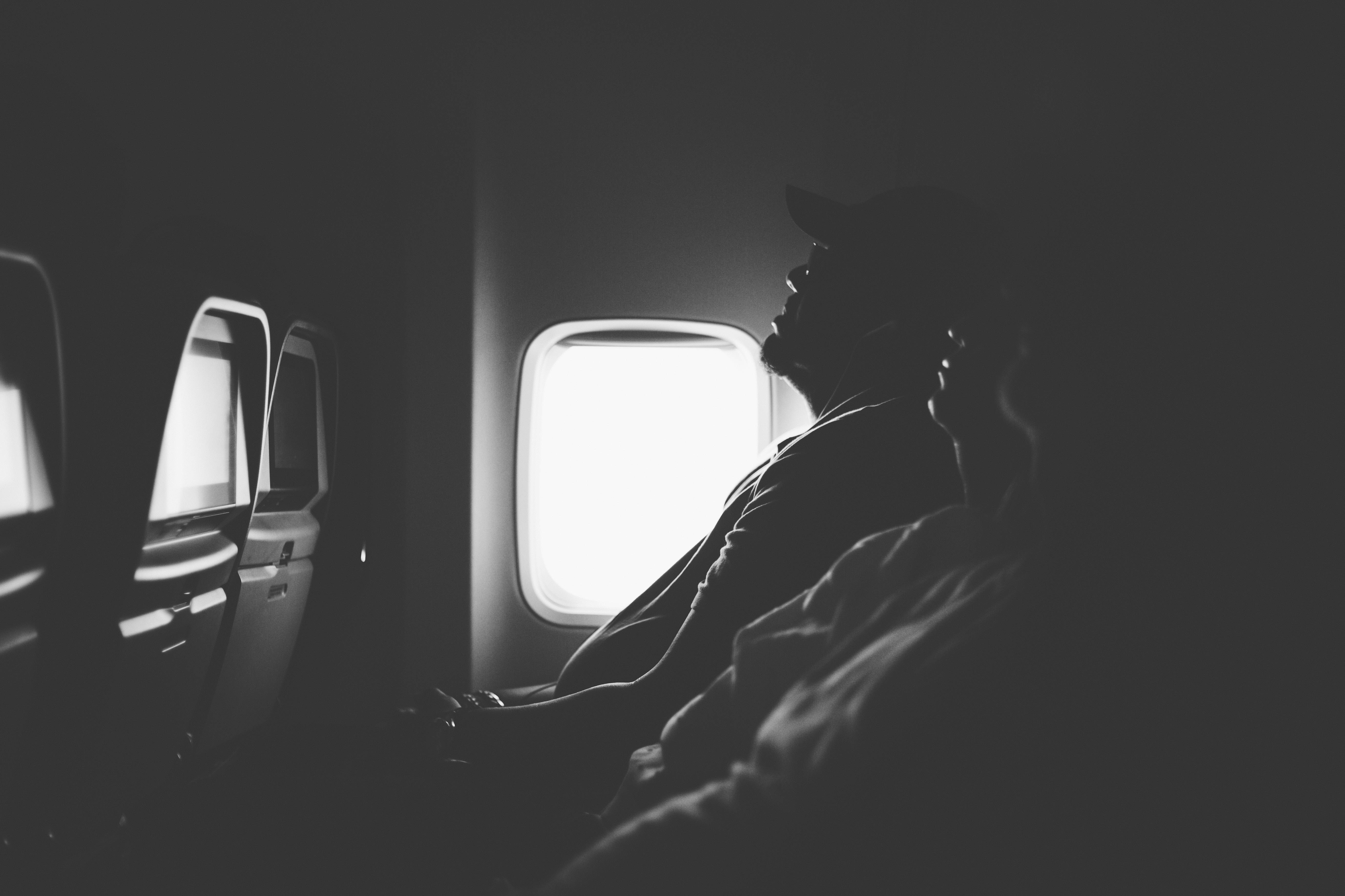 grayscale photo of three person sitting inside airplane