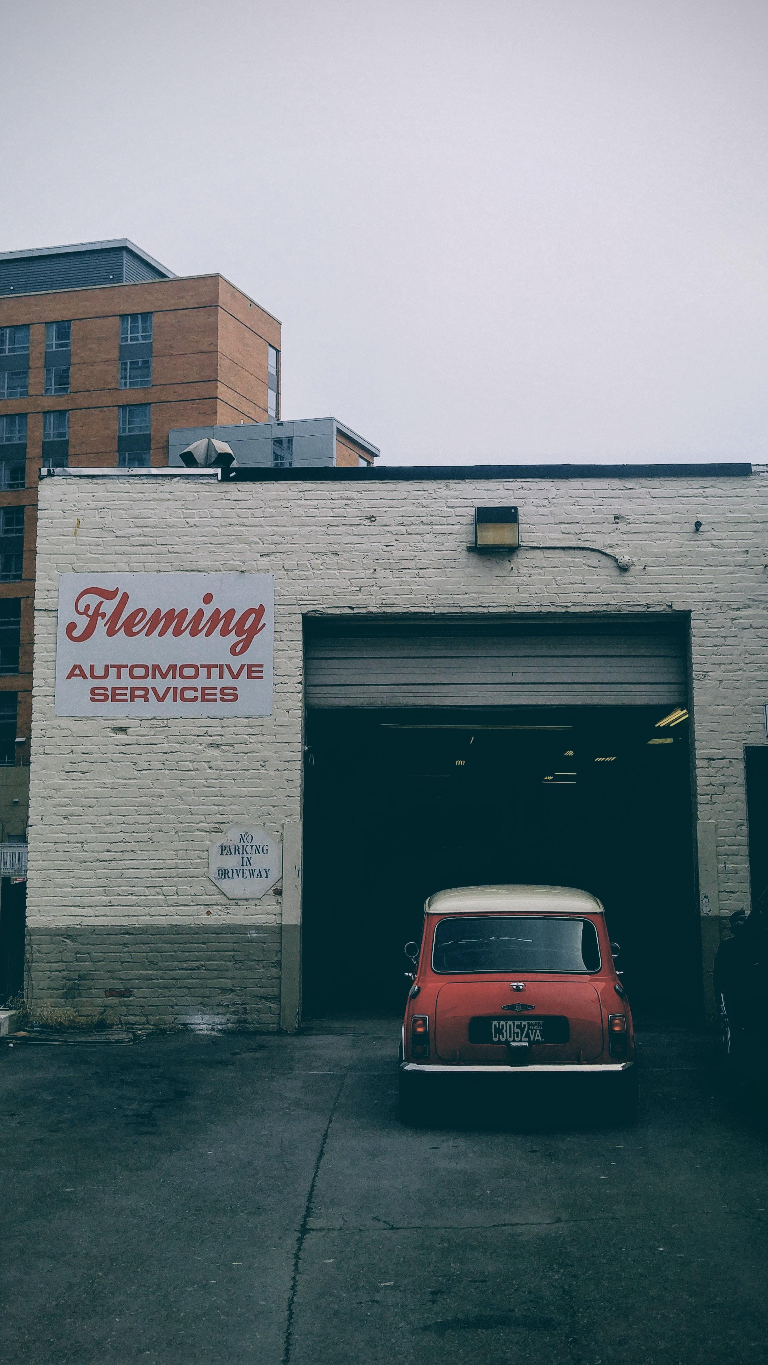 An older car going into a garage shop.