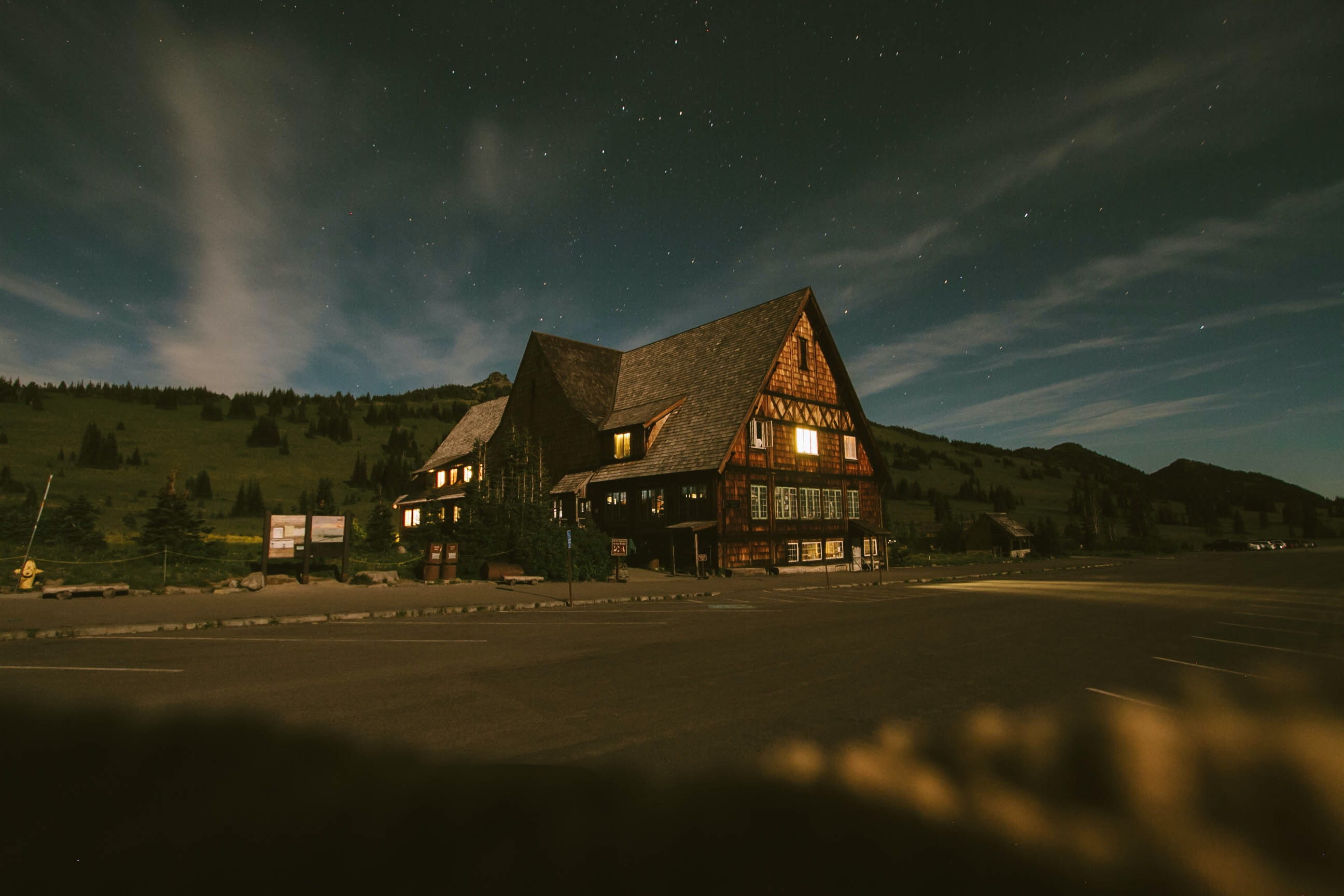 Large cabin-like house lit up from the inside at dusk in a field with mountains in the background