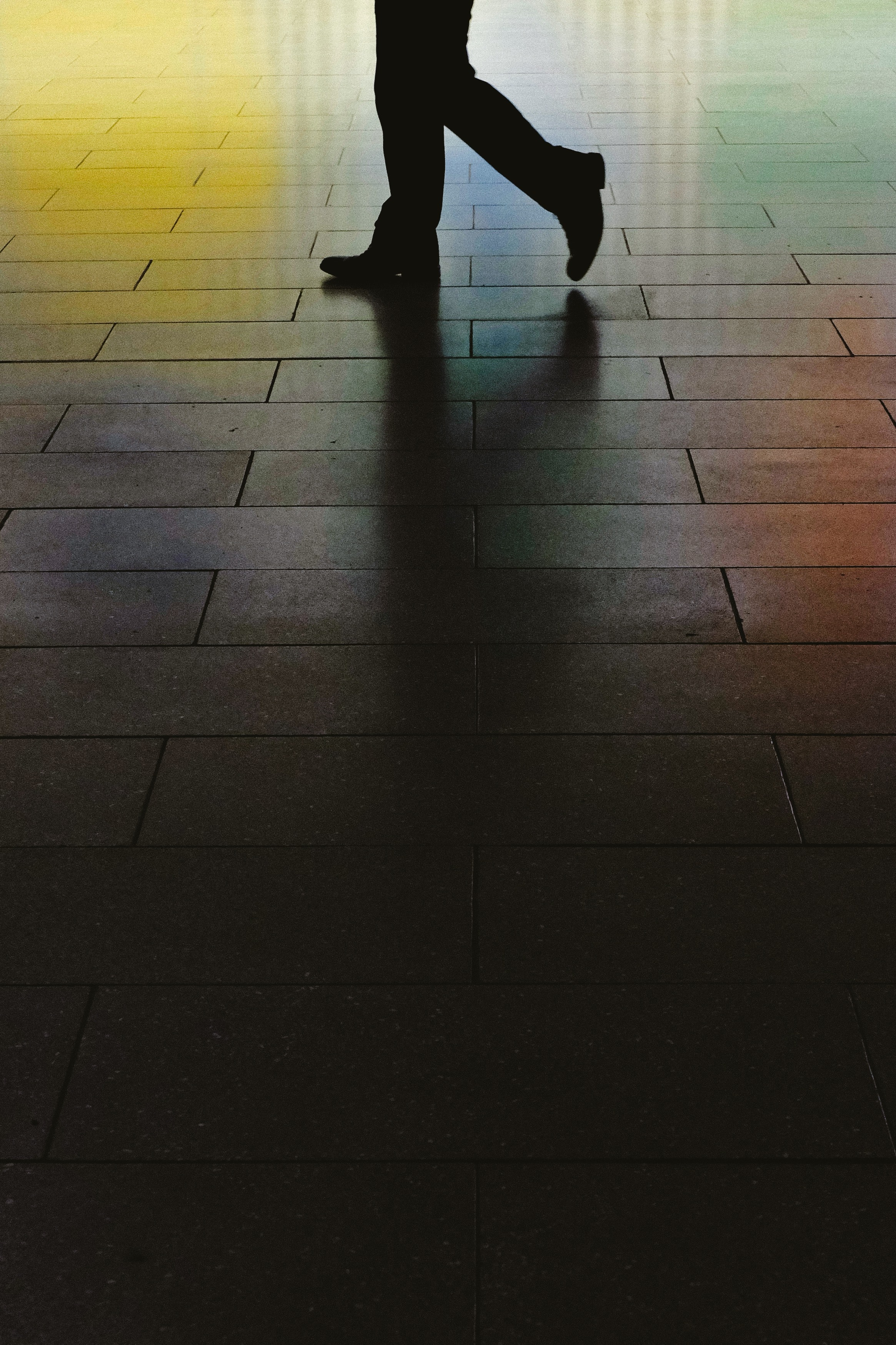 A low shot of a person's legs on a glossy sidewalk