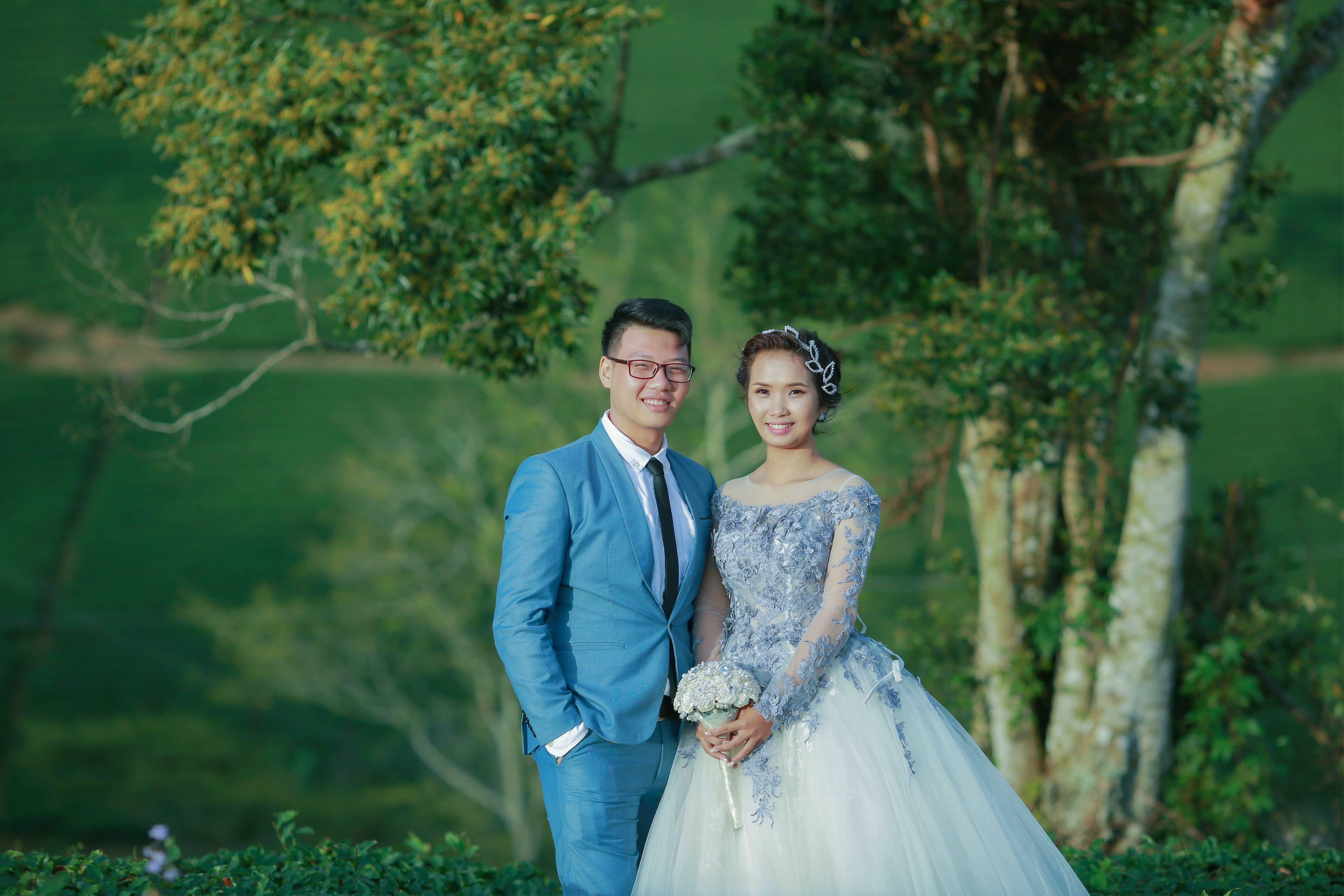 A bride and groom smile at the camera in front of green trees and bushes in Vietnam