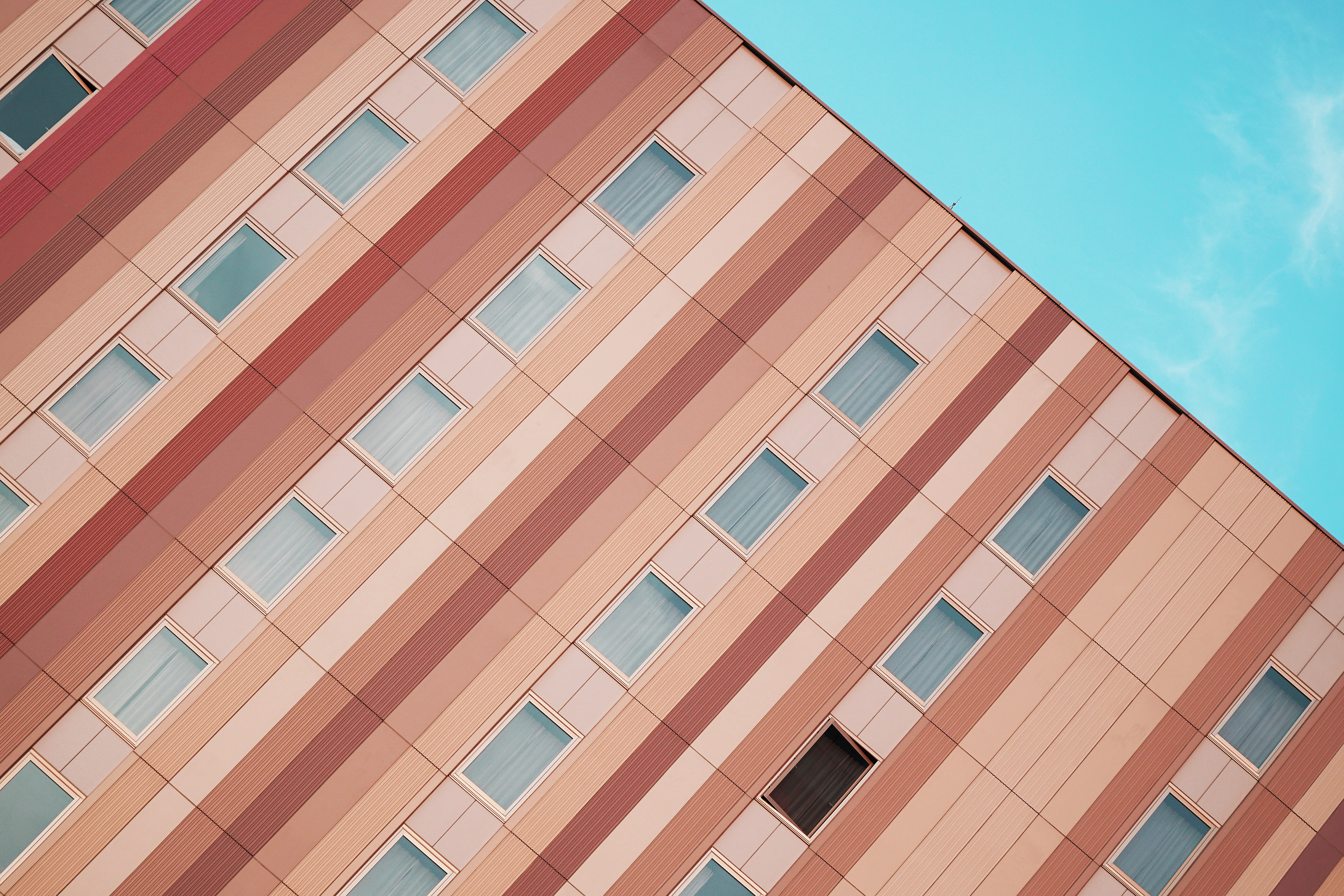 An angular shot of a residential building facade painted with pastel-colored stripes