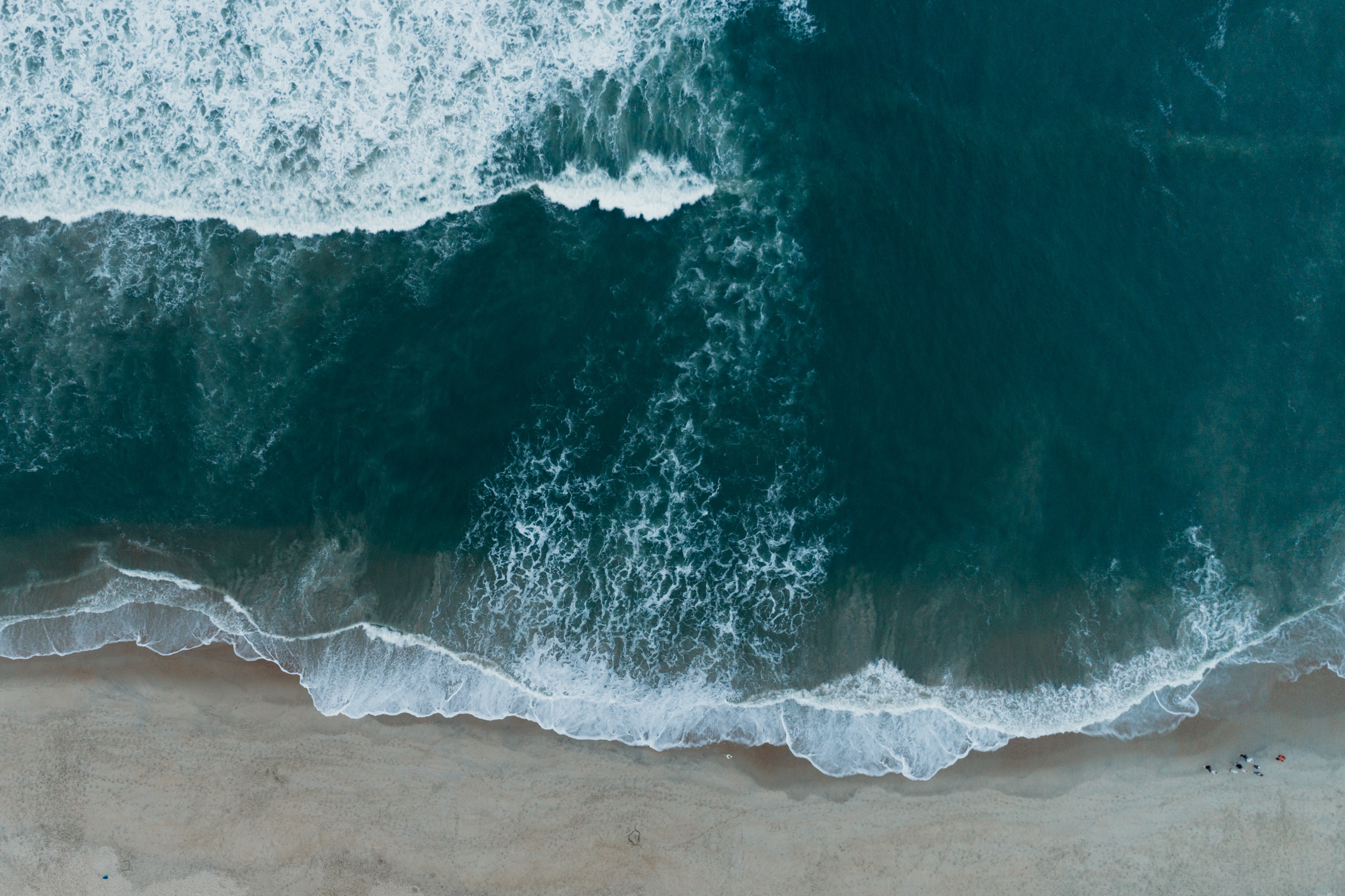 Drone view of the ocean washing on the sand beach shore at Nags Head, North Carolina, United States