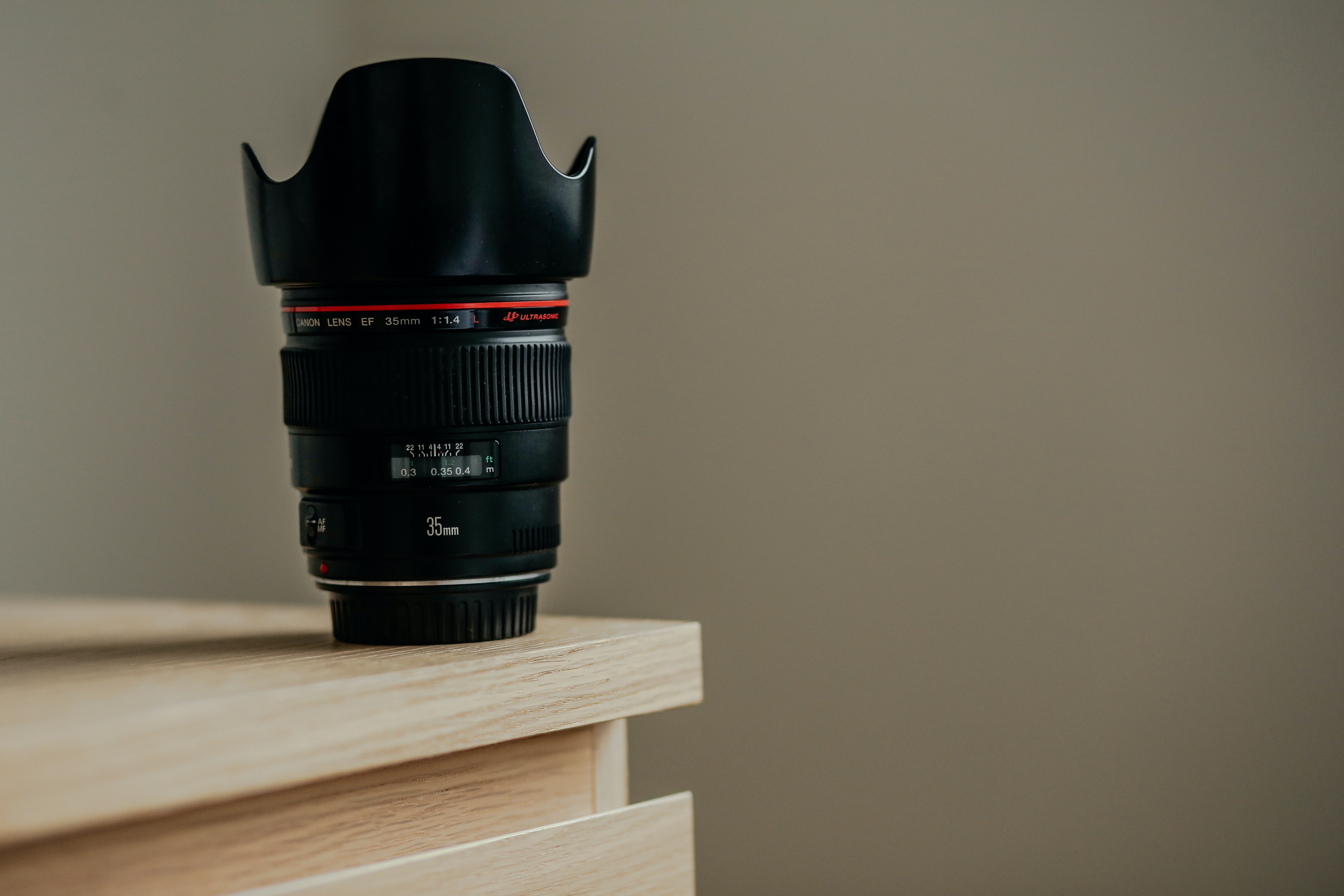 A long camera lens on the edge of a wooden surface