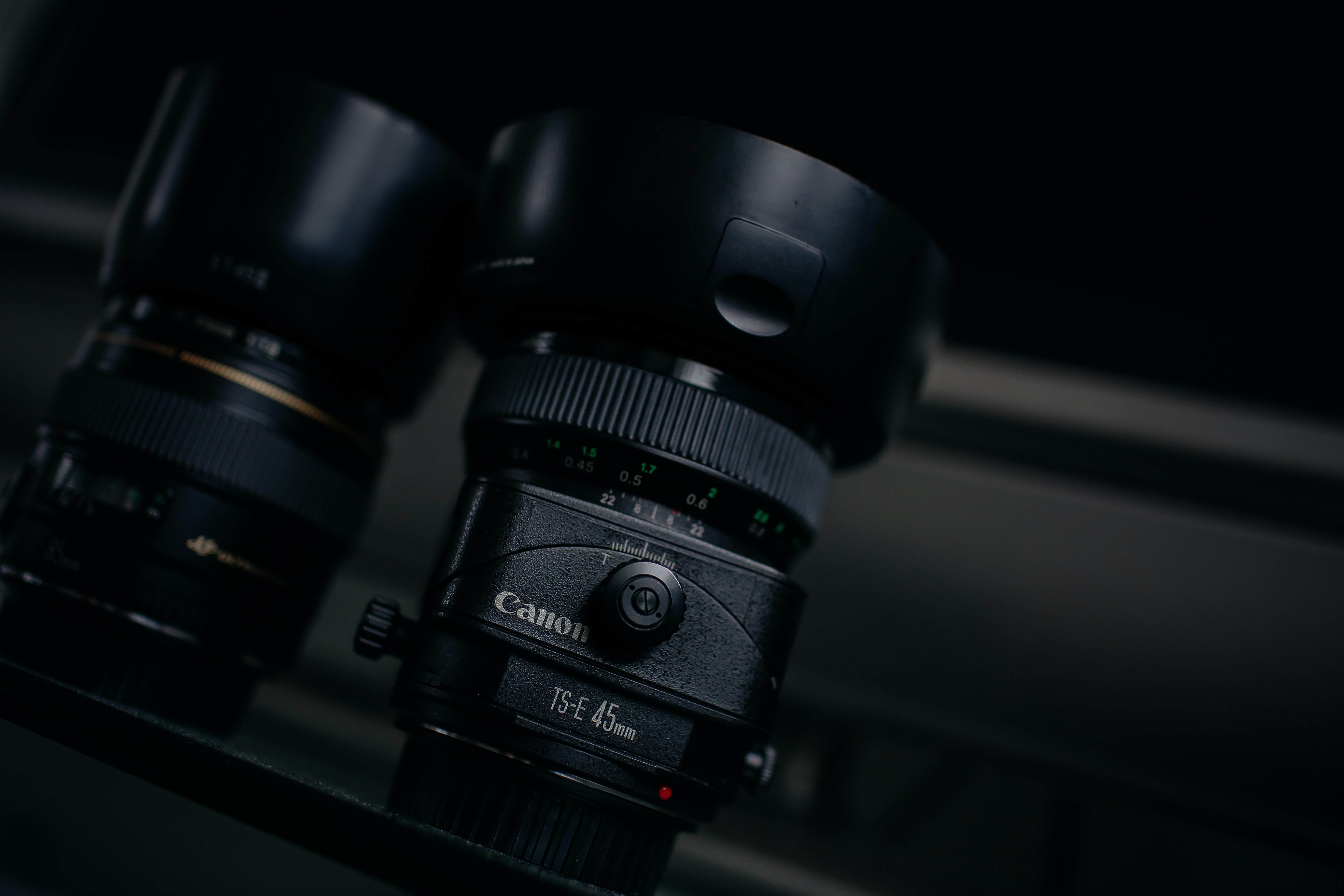 Canon 45mm lens beside another lens on a shelf