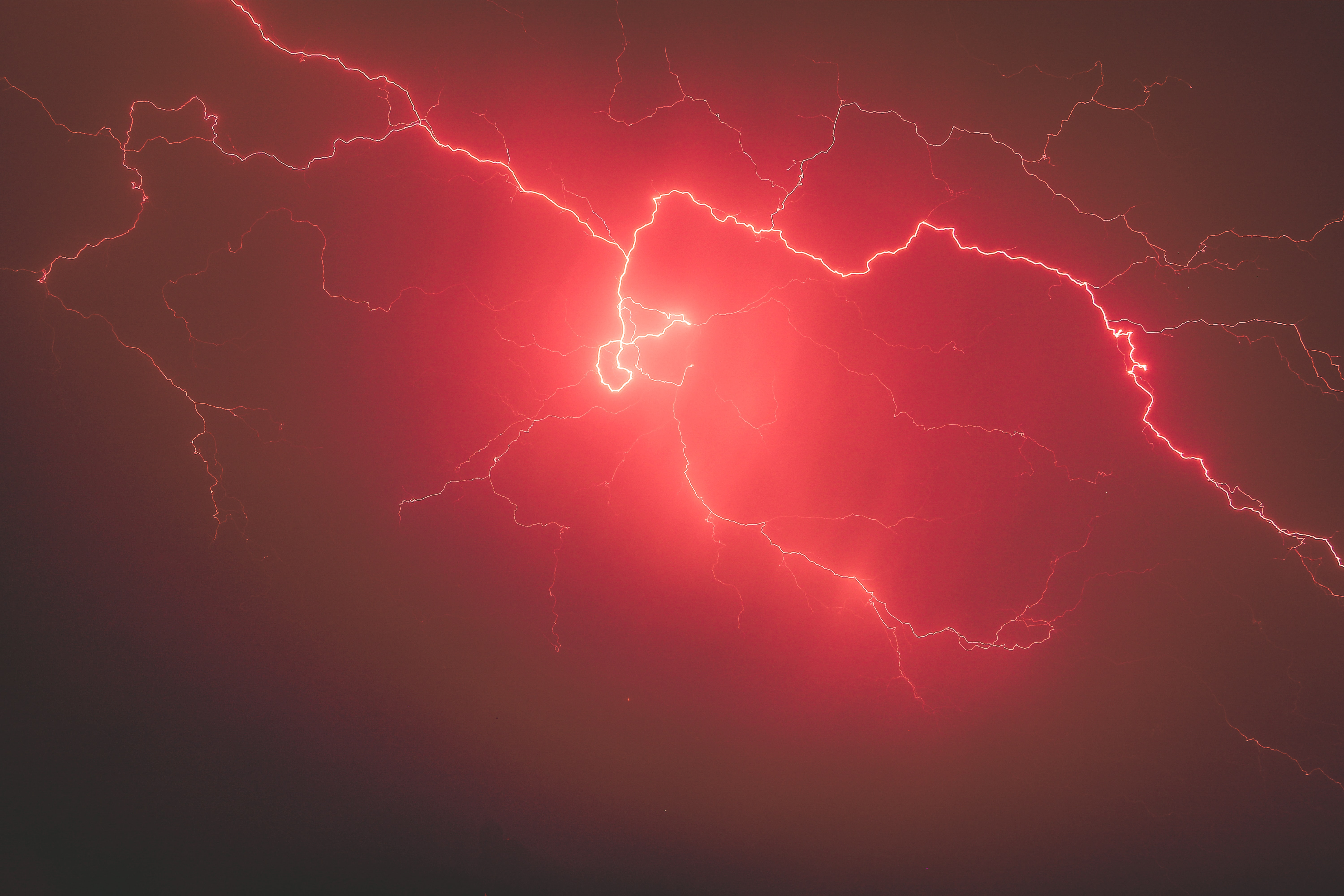 Bright red lightning bolts in the night sky during a storm near St. Paul's School