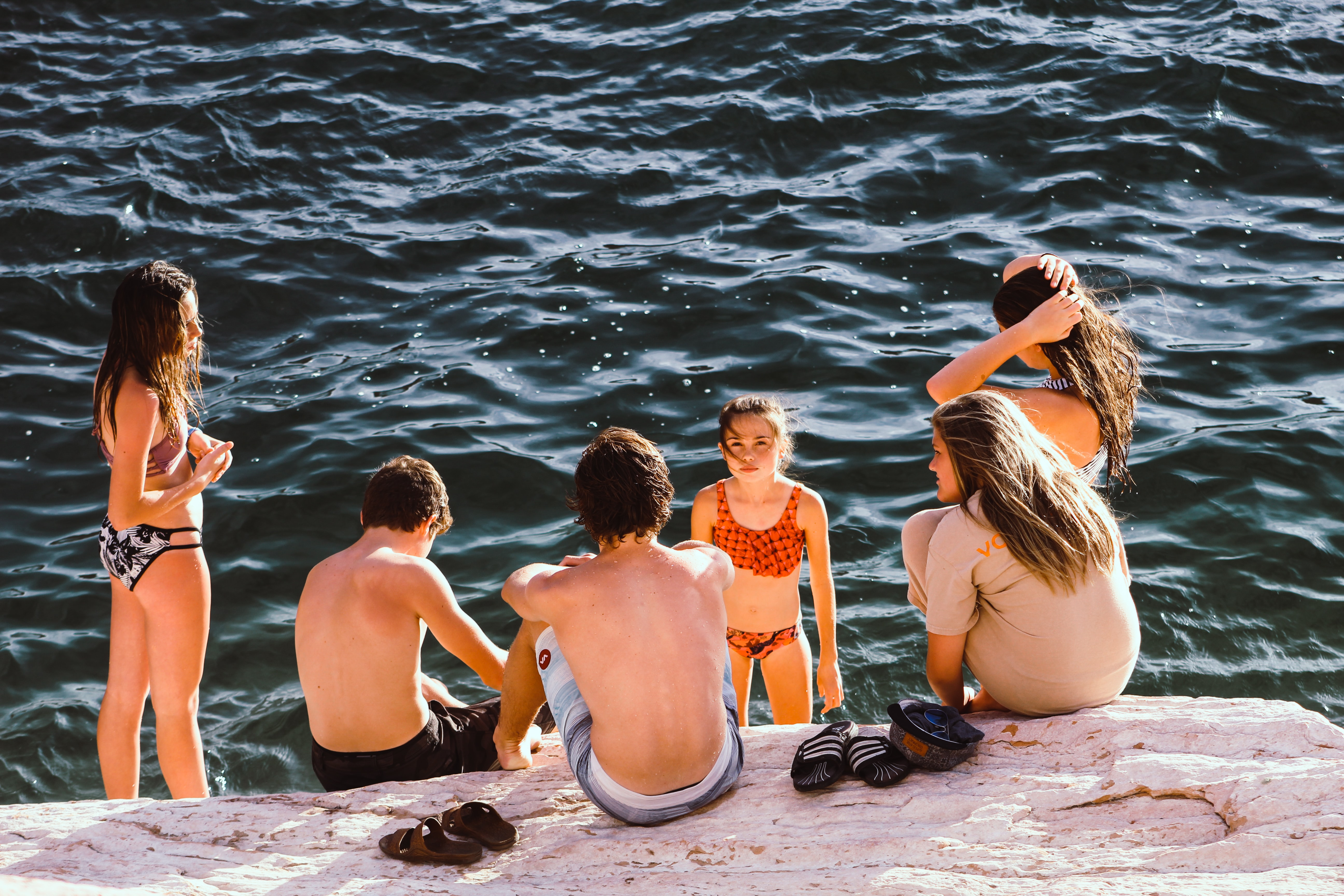 Family with children in swimsuits sitting on the rocks of a beach getting ready to swim