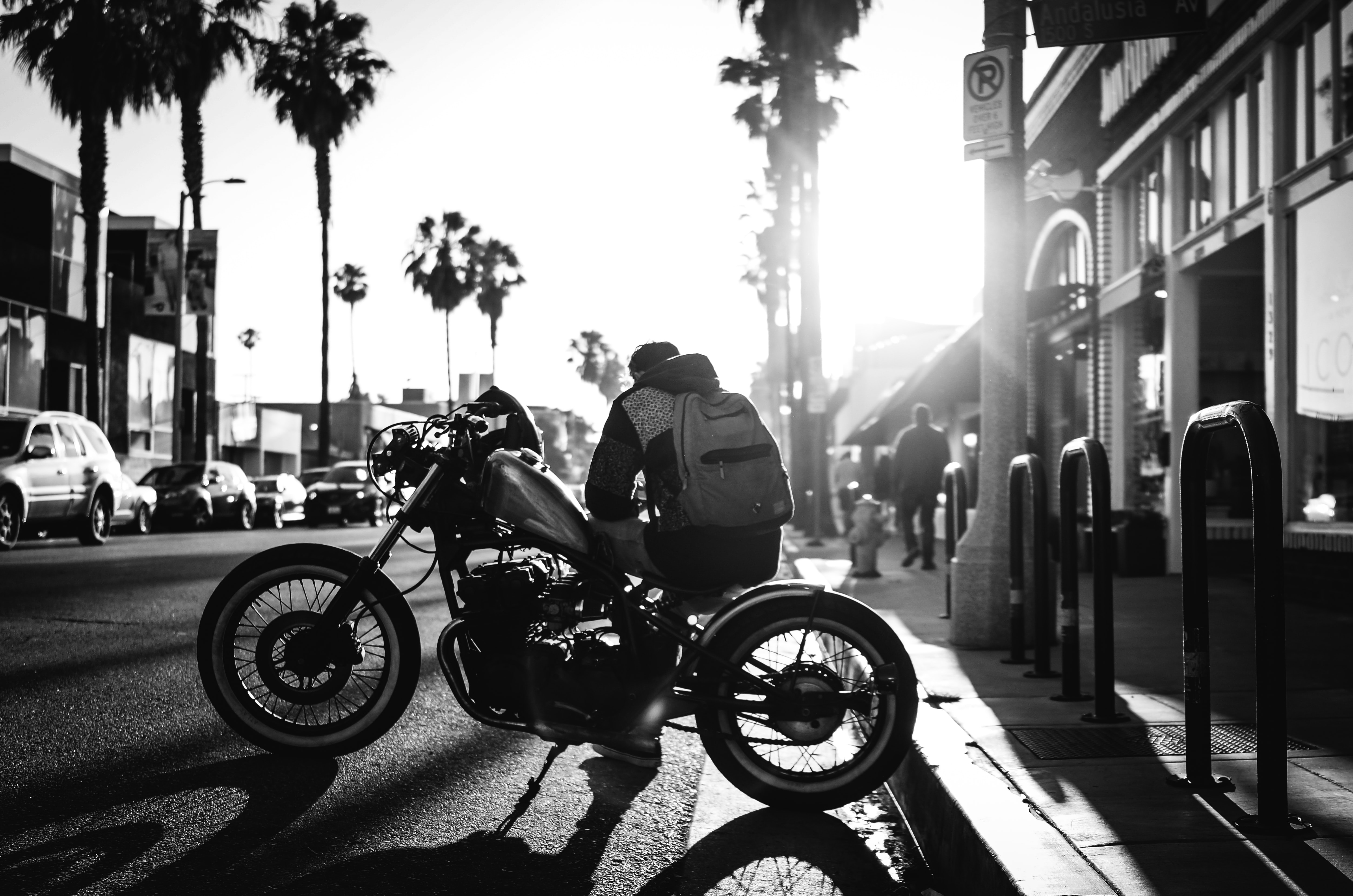 Black and white shot of man with backpack sitting on motorbike with palm trees, Venice