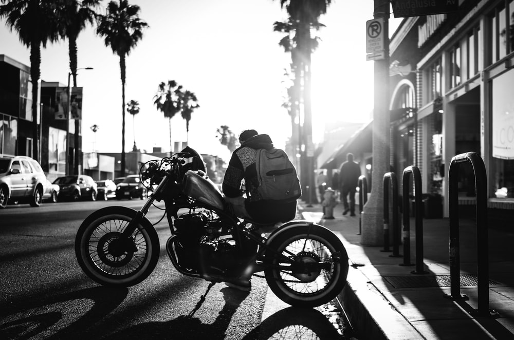 man sitting on cruiser motorcycle on grayscale photograyphy