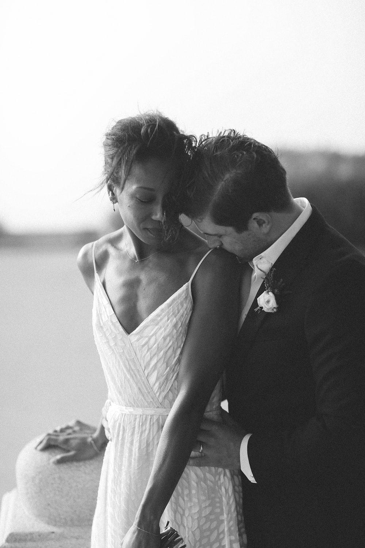man kissing shoulder of woman