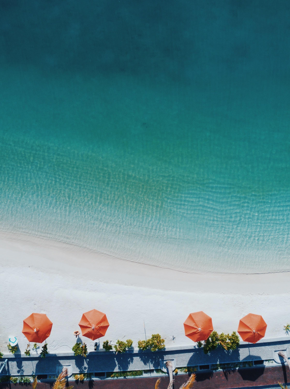 aerial photography of four orange patio umbrellas on seashore