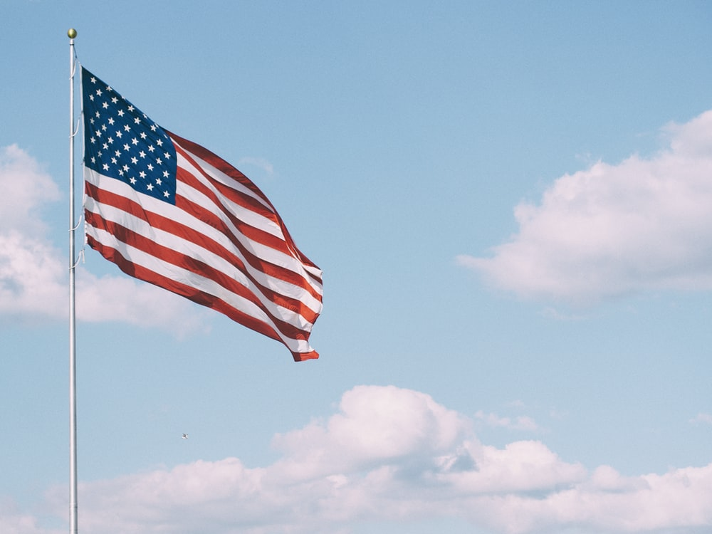 flag of U.S.A. under white clouds during daytime