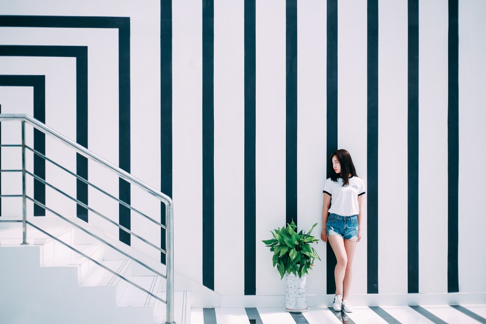 woman leaning on black and white wall