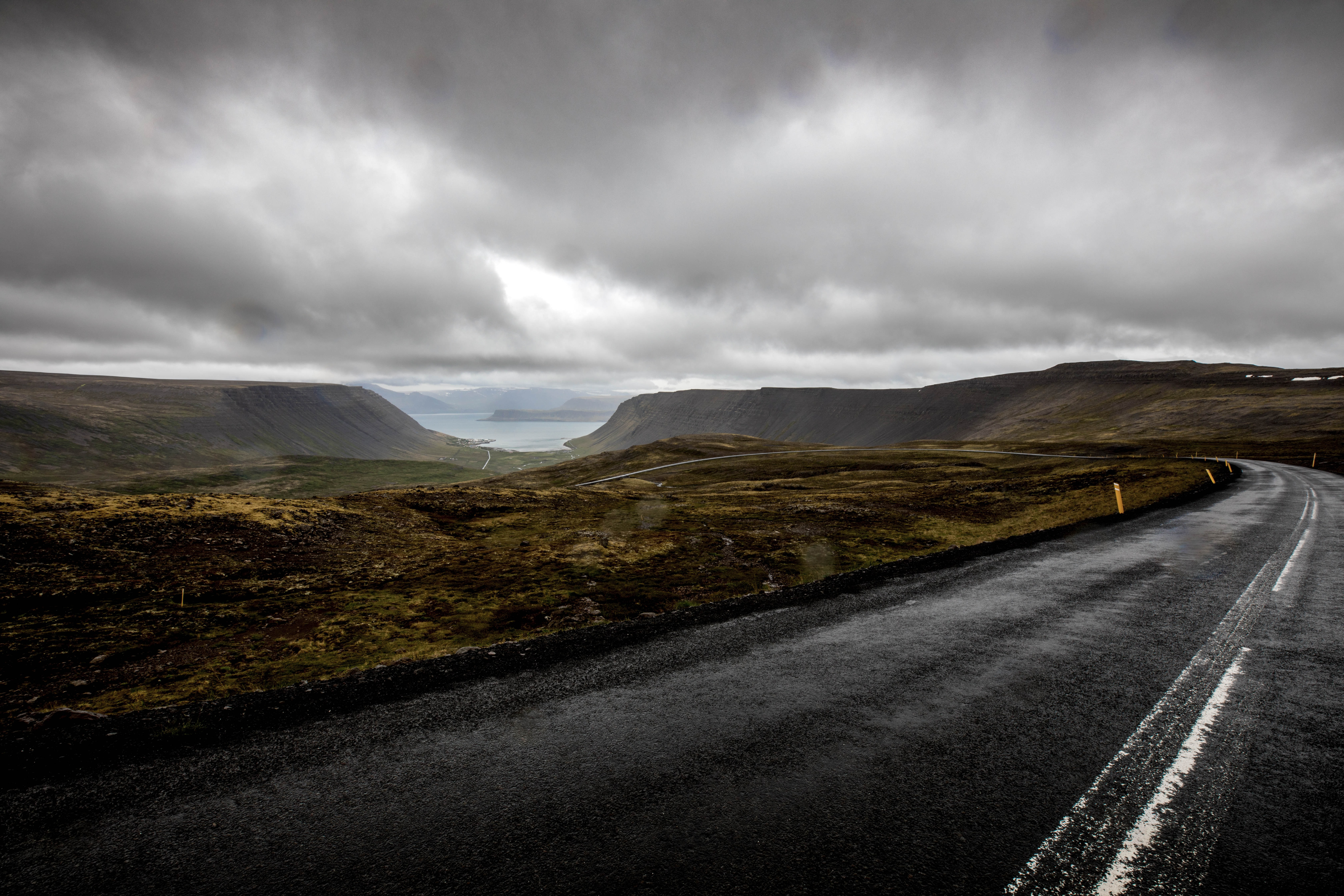 gray asphalt road near mountains under cloudy sky during daytime