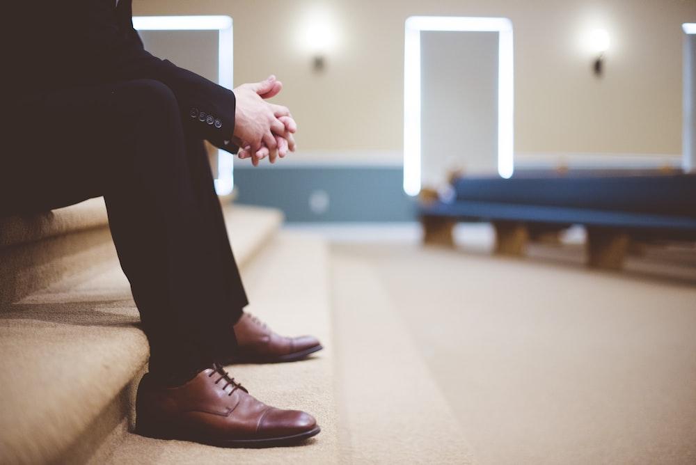 部屋の中の茶色のカーペットの階段に座っている黒いズボンと茶色の革のレースアップシューズの男