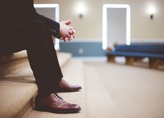 man in black pants and pair of brown leather lace-up shoes sitting on brown carpeted stairs inside room