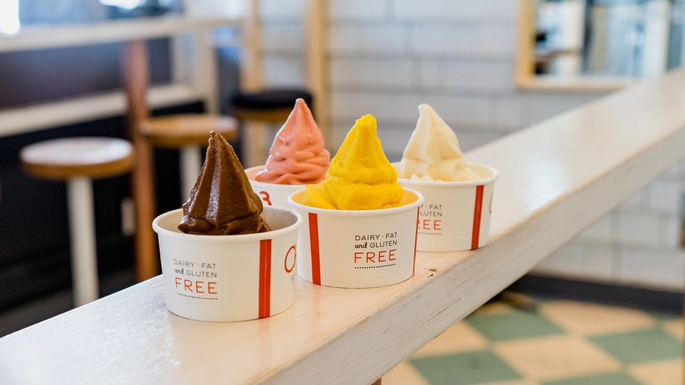 four assorted flavor of ice cream on white wooden table