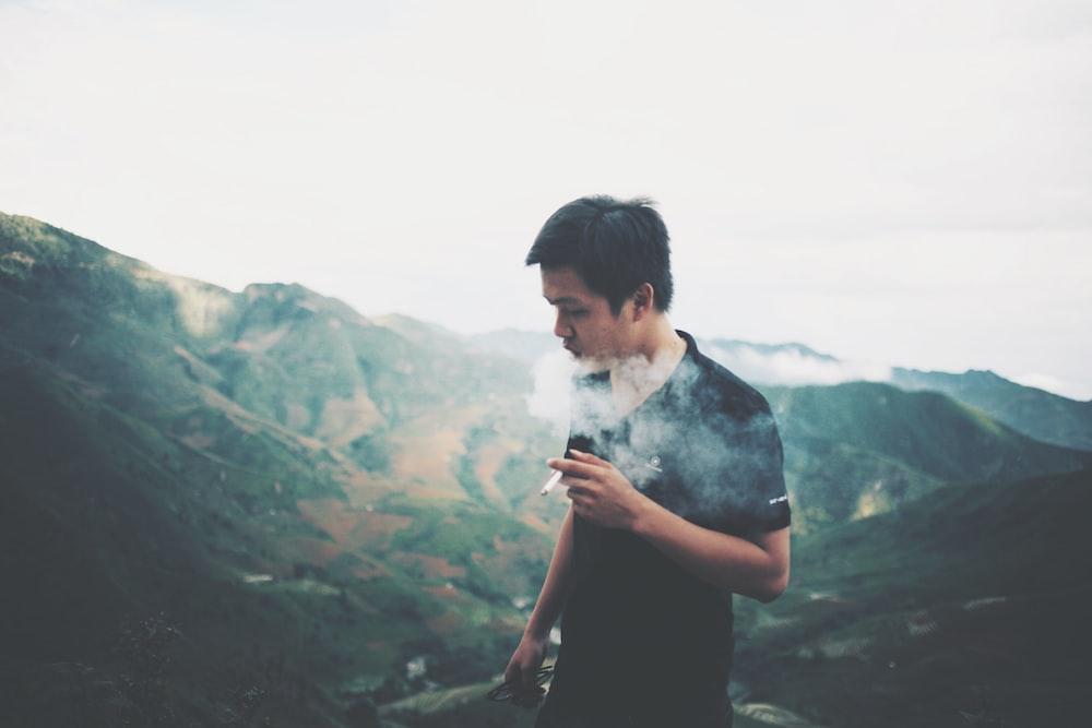 man smoking on mountain summit