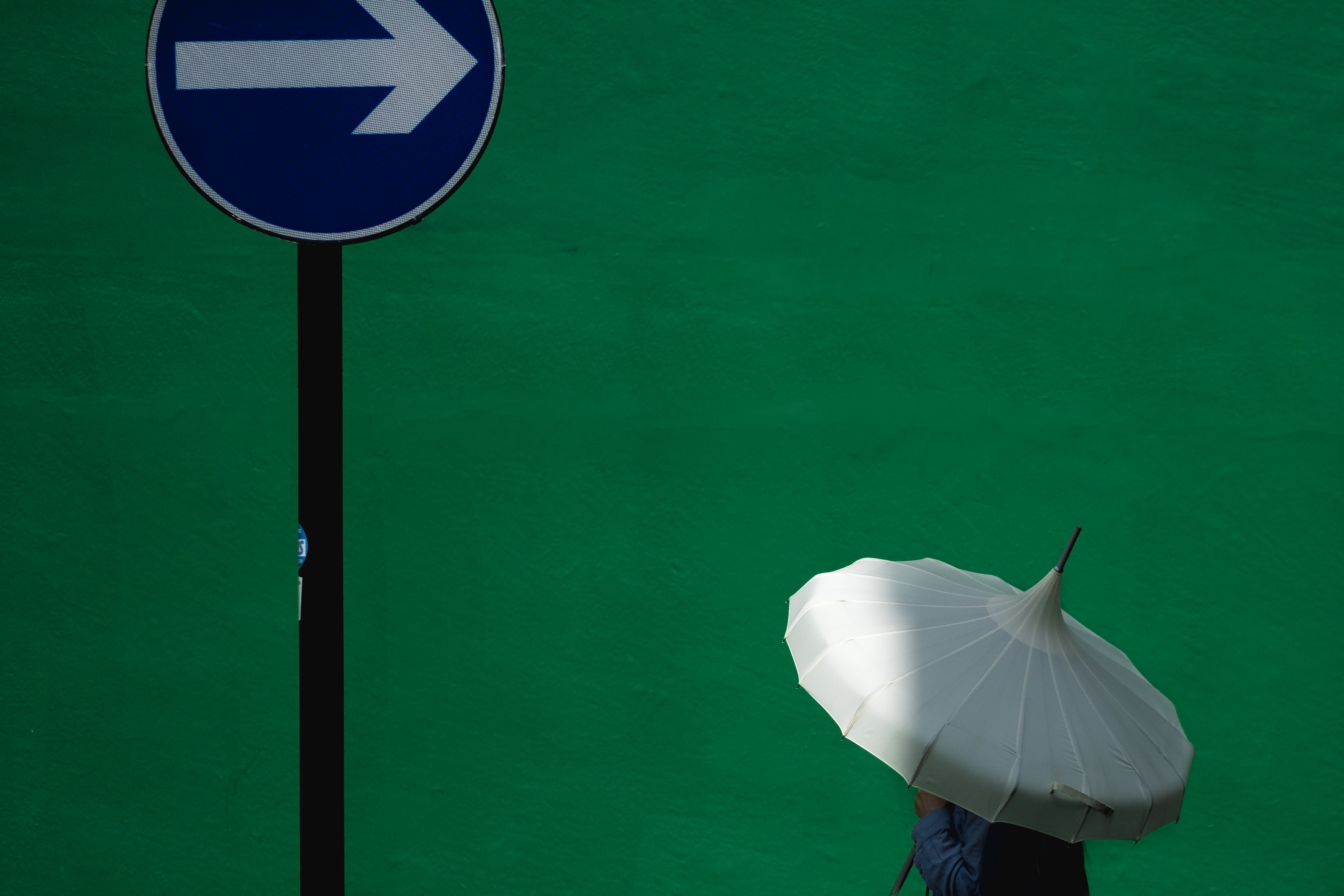 person using white umbrella near blue road signage