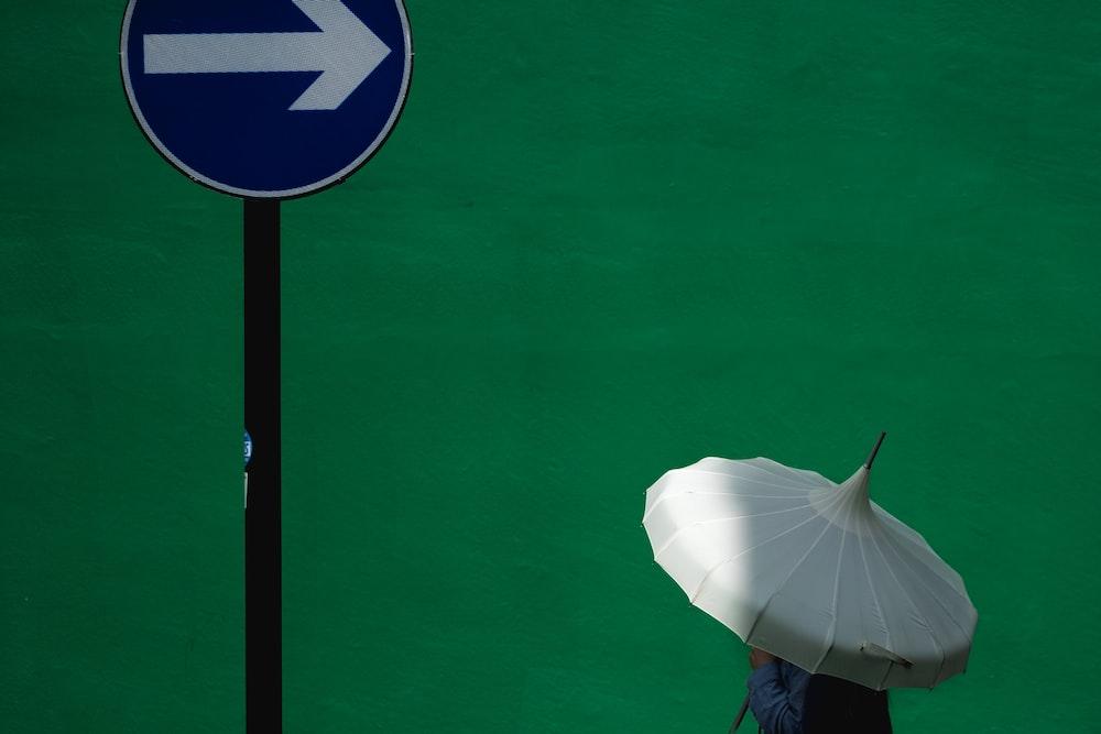 person using white umbrella near blue road signage