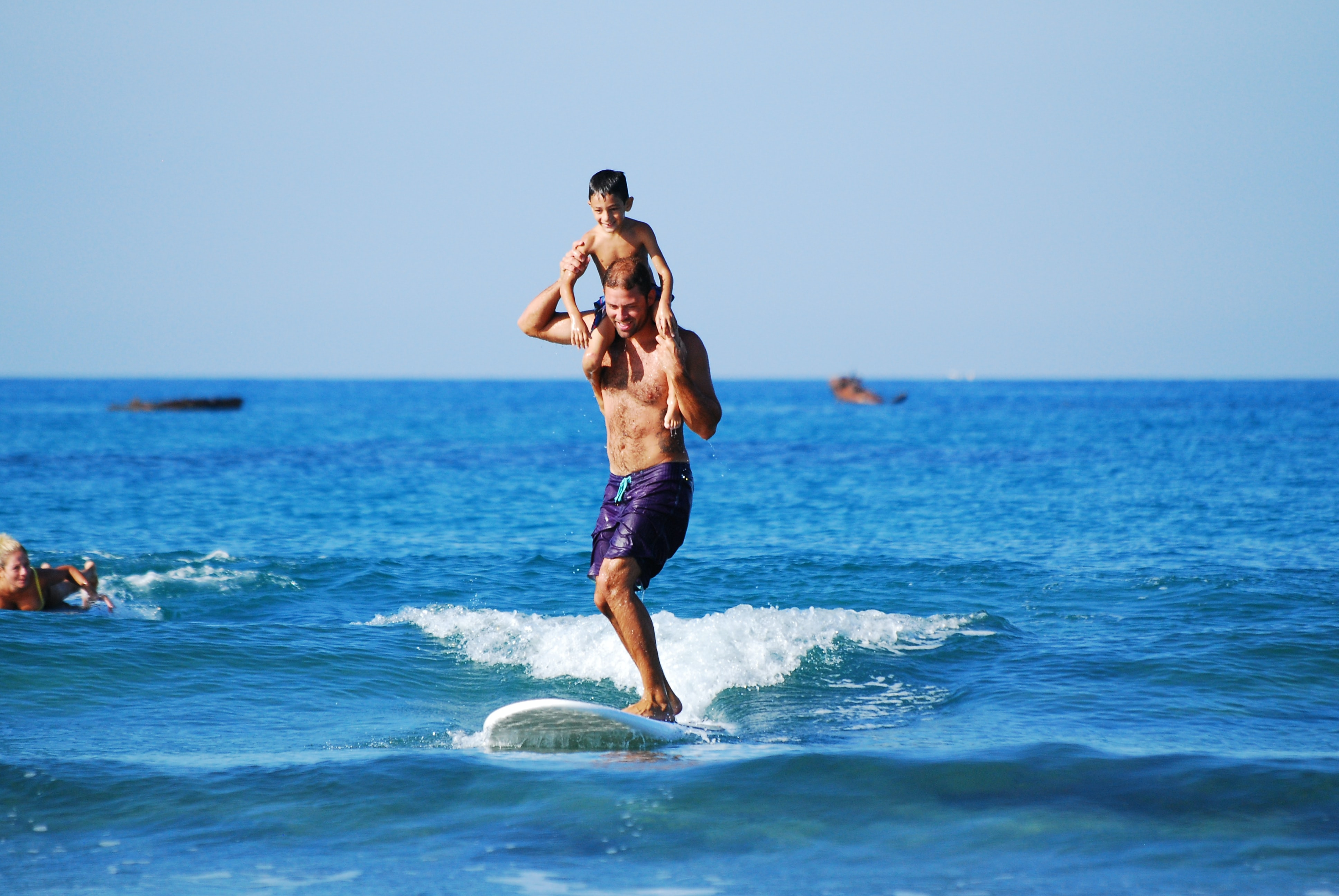 Boy on his father's shoulders, who is surfing on a board