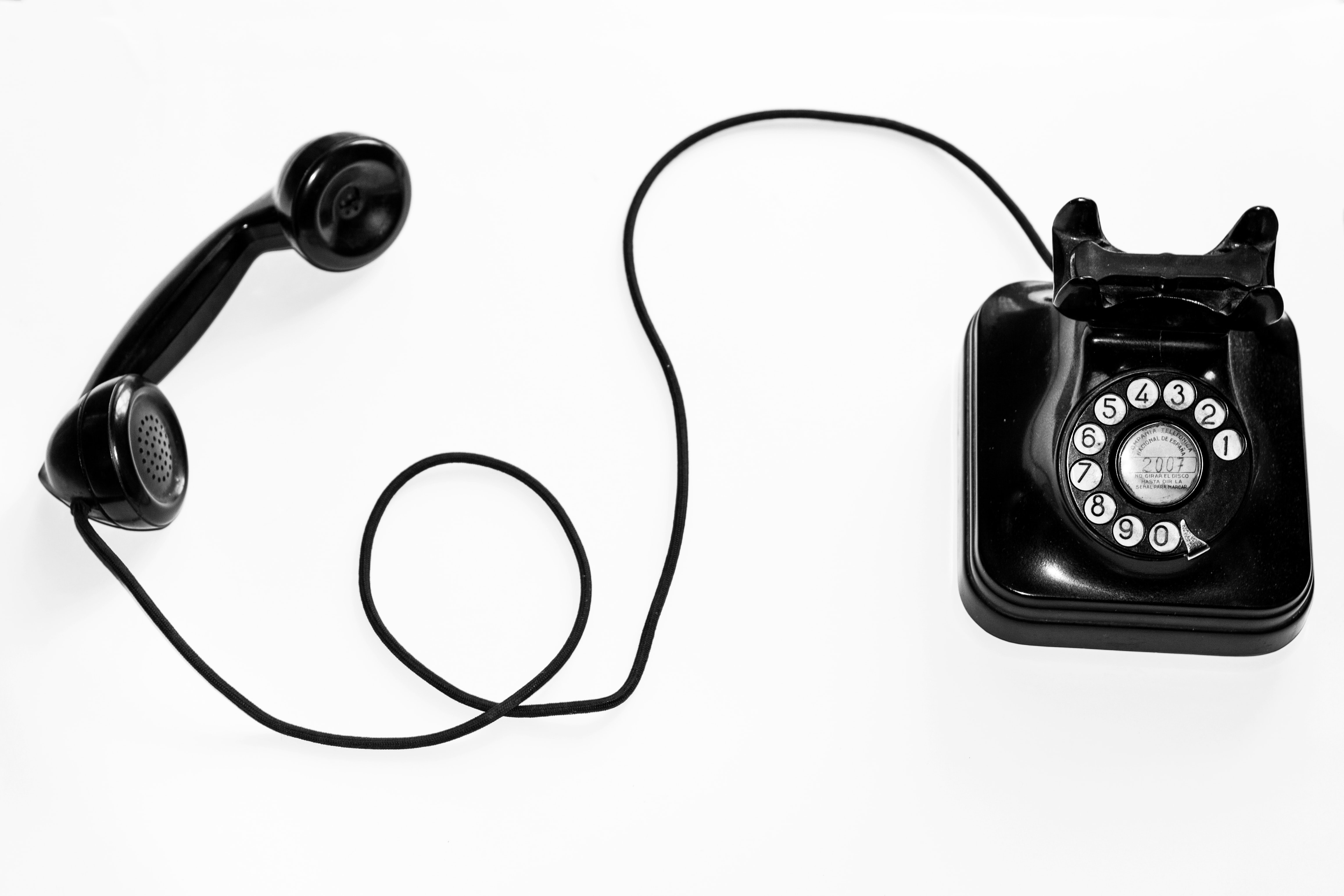 photo of black rotary phone against white background