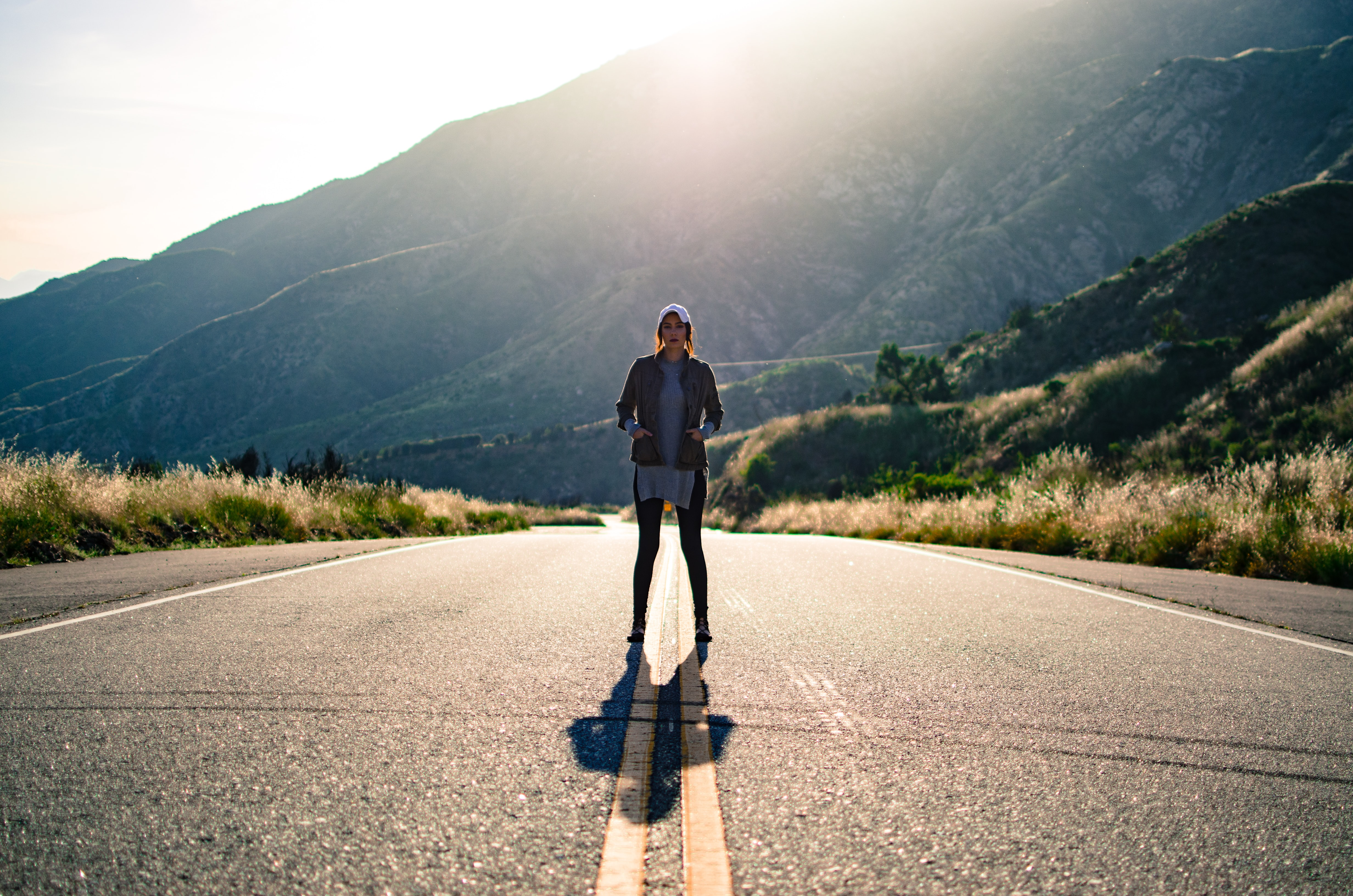 worm's eye view photography of woman standing in the middle of the road surrounded of trees and mountain