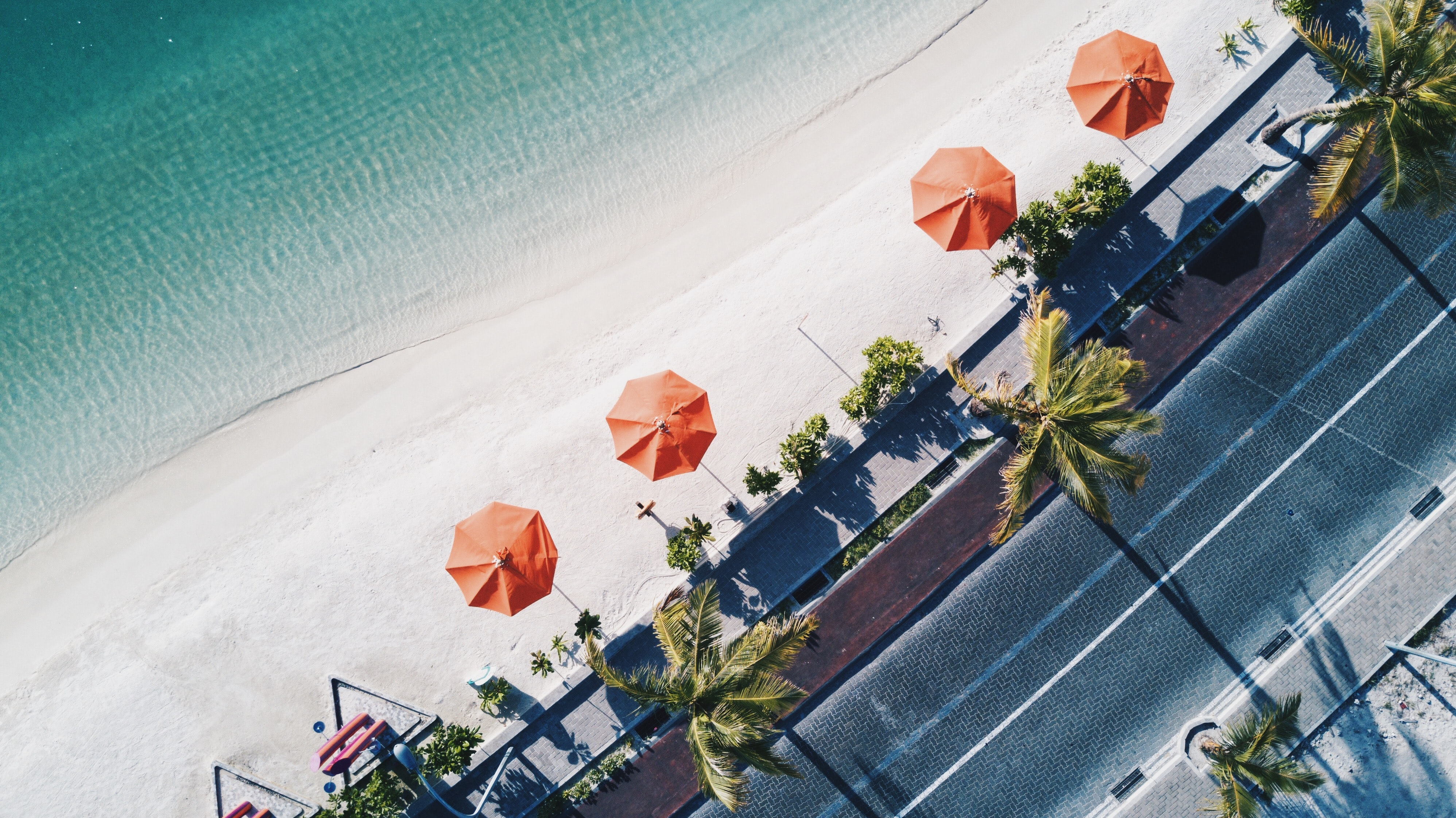 Drone aerial view of footpath, palm trees, and sun umbrellas by the sand beach in Rasfannu