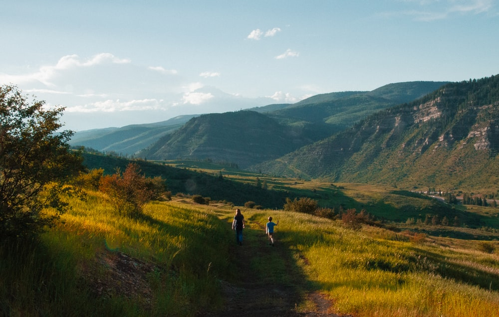 boy and man walking on mountain hill