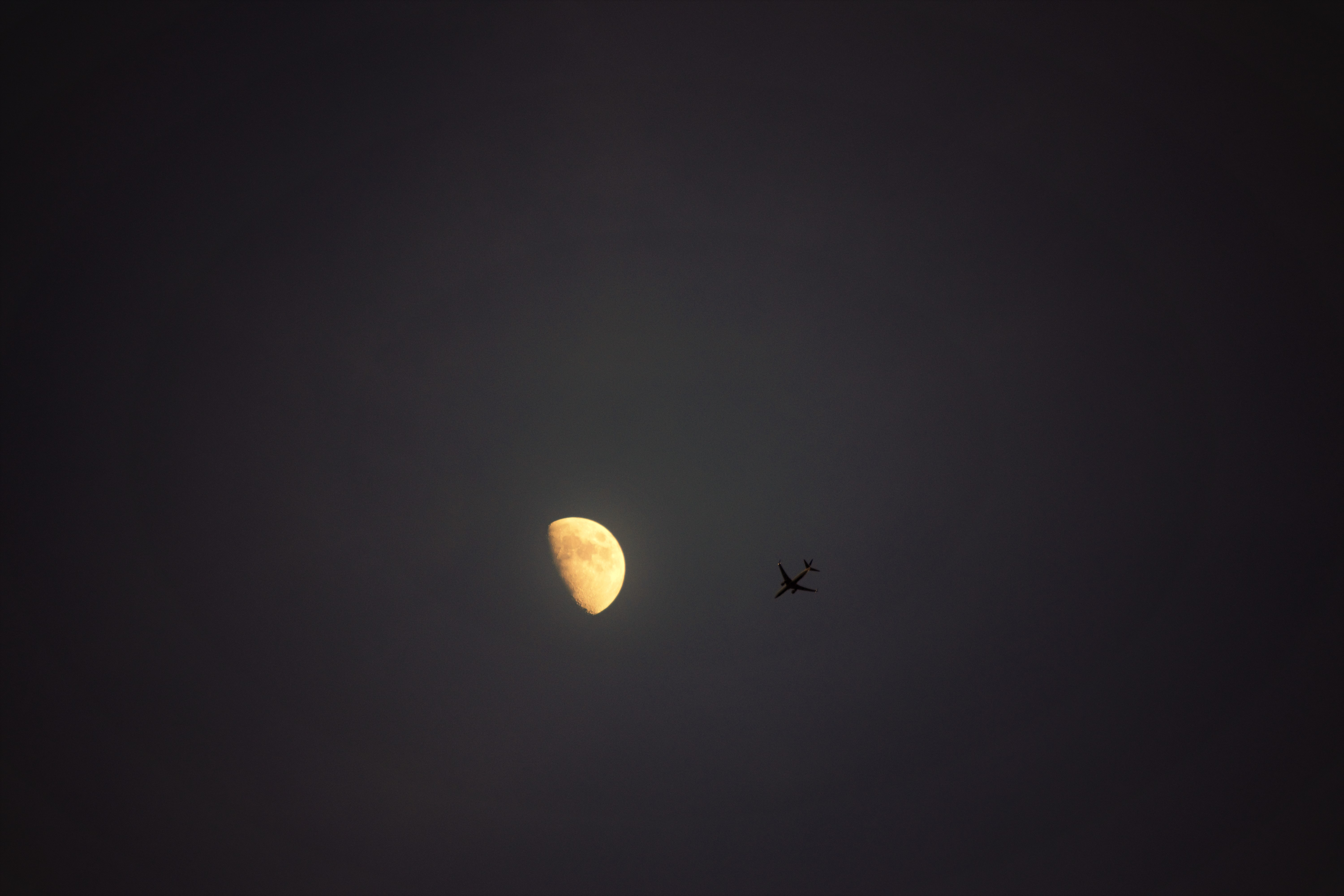 The night sky with a half moon and a plane flying by