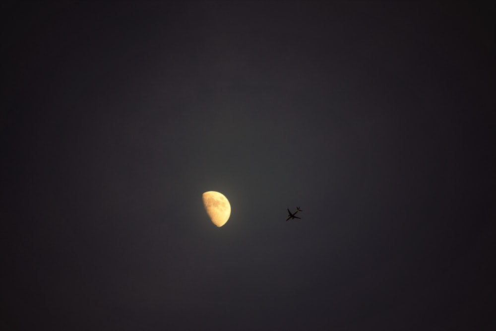 silhouette of airplane under half moon during nighttime