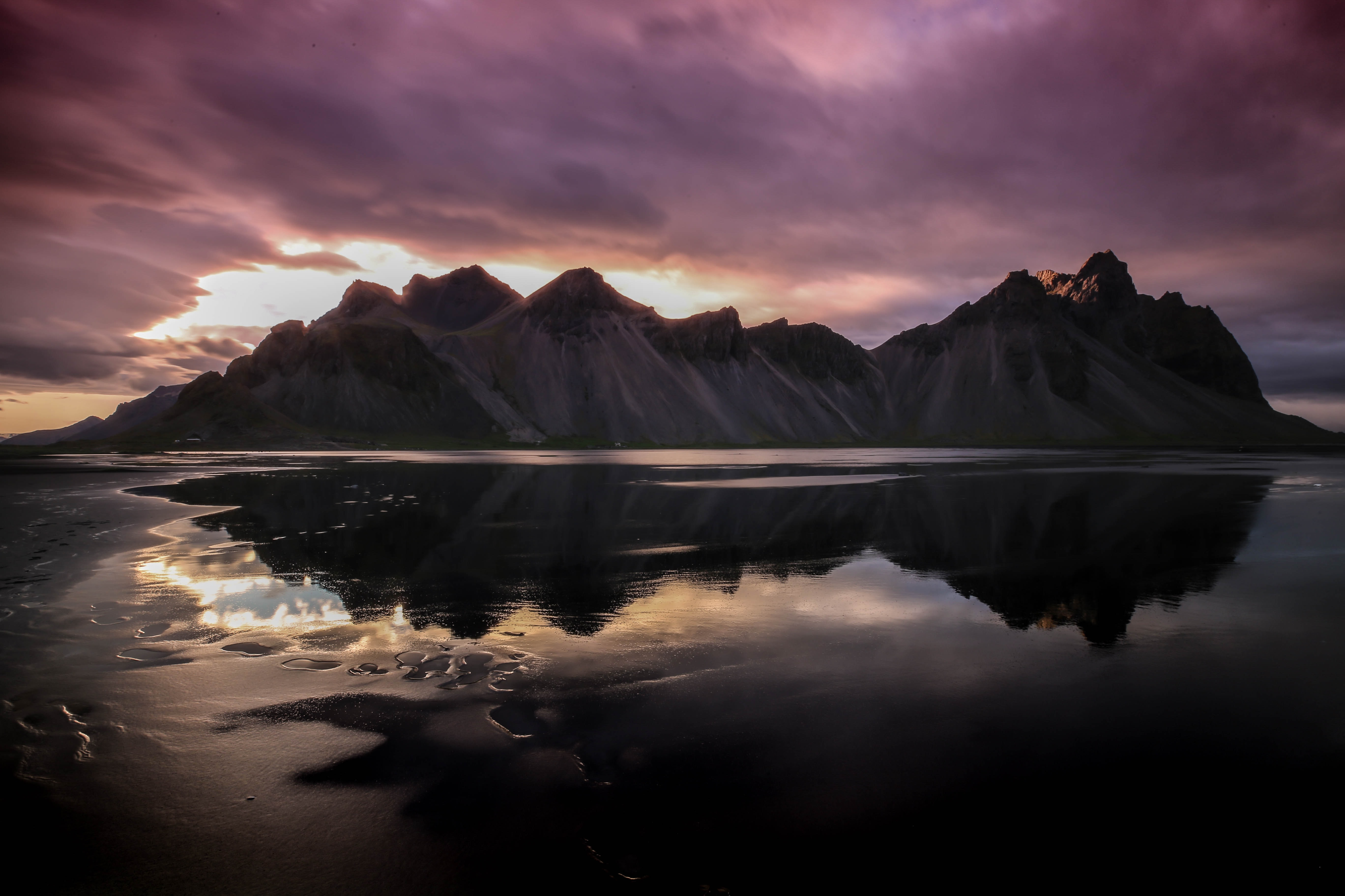 Smooth eroded mountains reflected in a half-frozen lake in Höfn