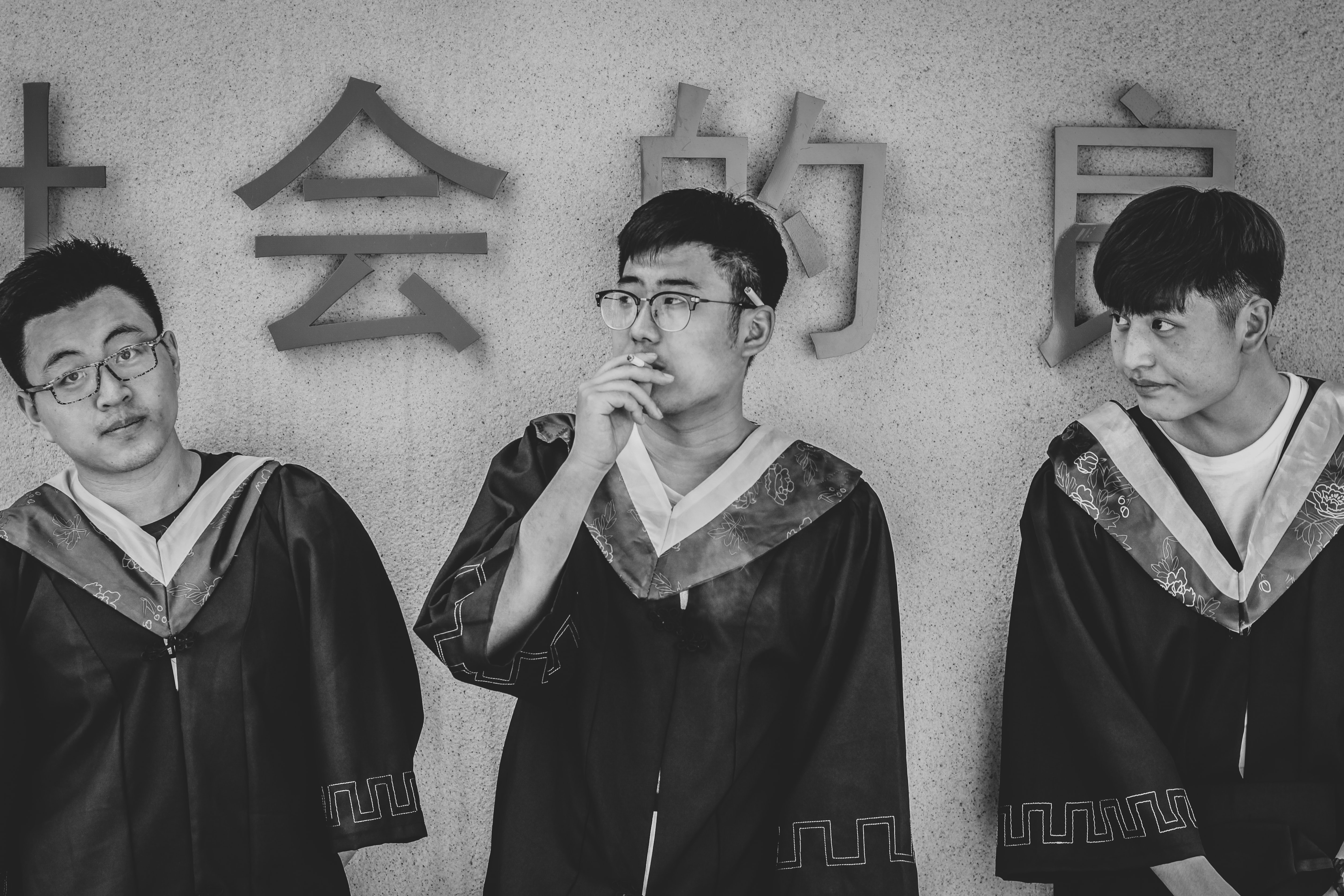 Three young men in graduation robes are standing next to a wall.