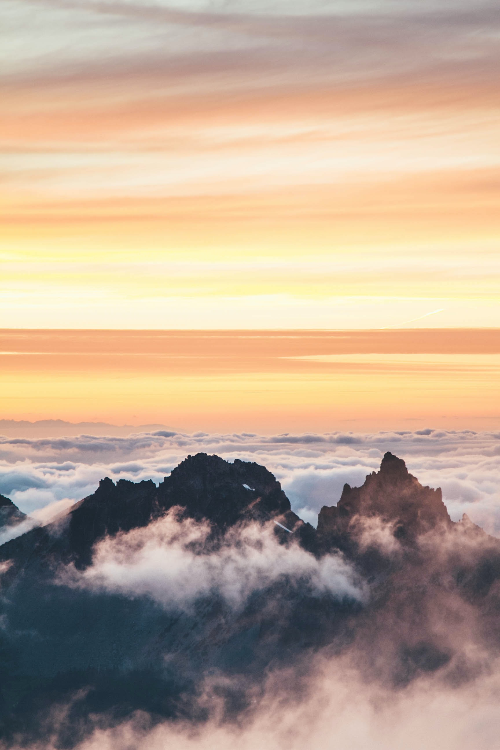 Jagged mountain peaks emerge from a sea of clouds during sunset
