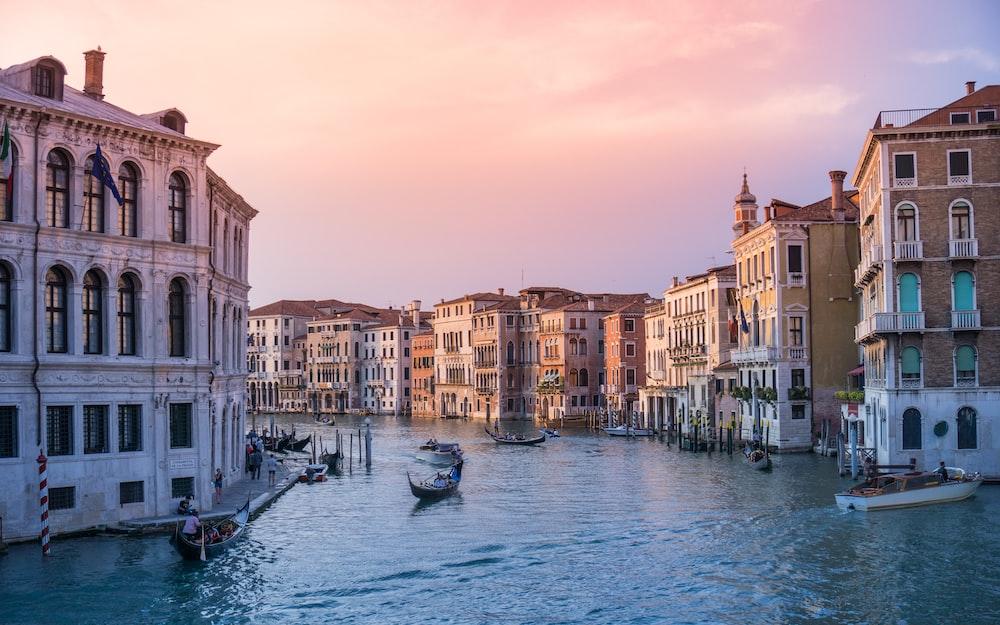 photo of gondolas on body of water between buildings