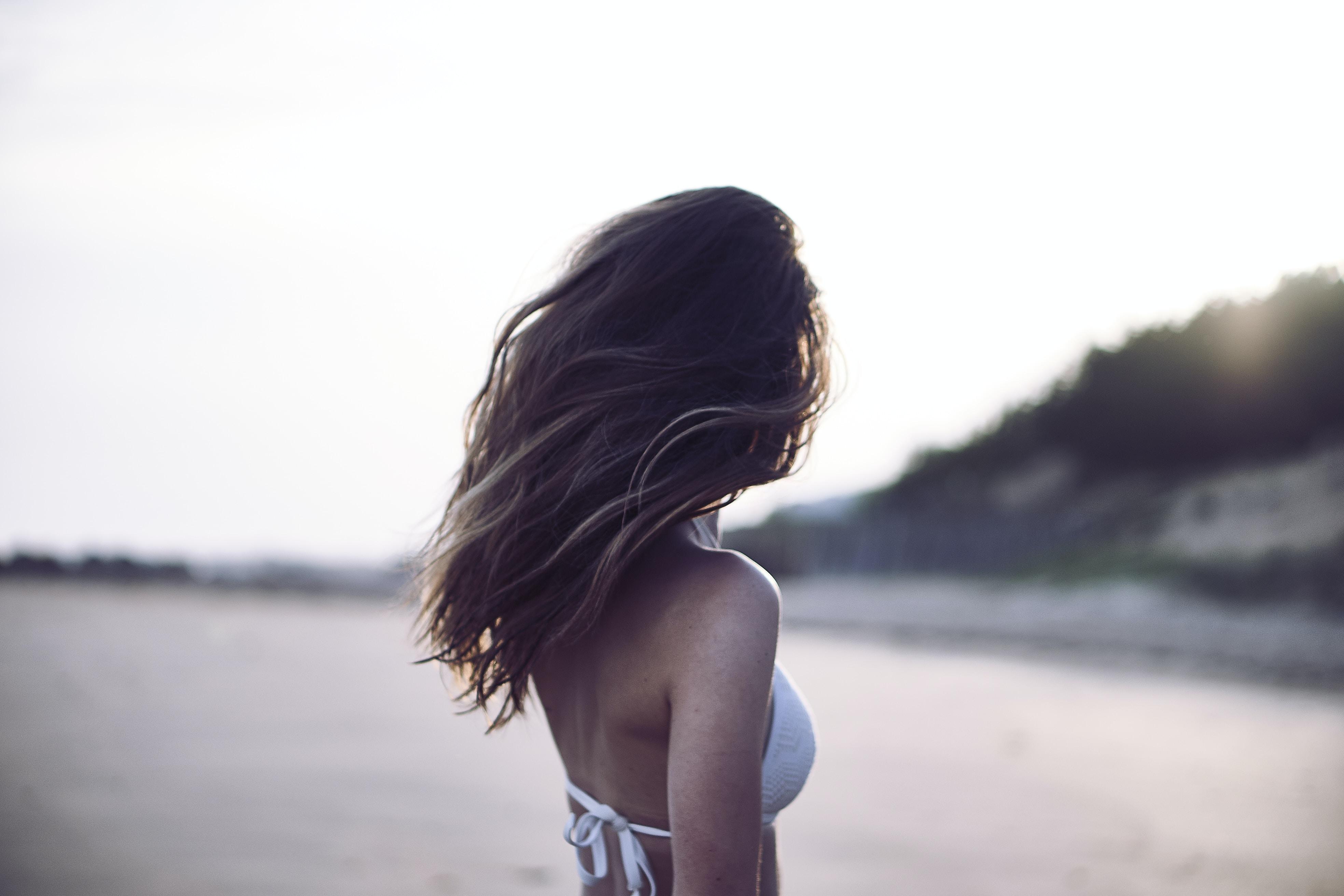 Woman with long brown hair in white bikini posing at La Grière