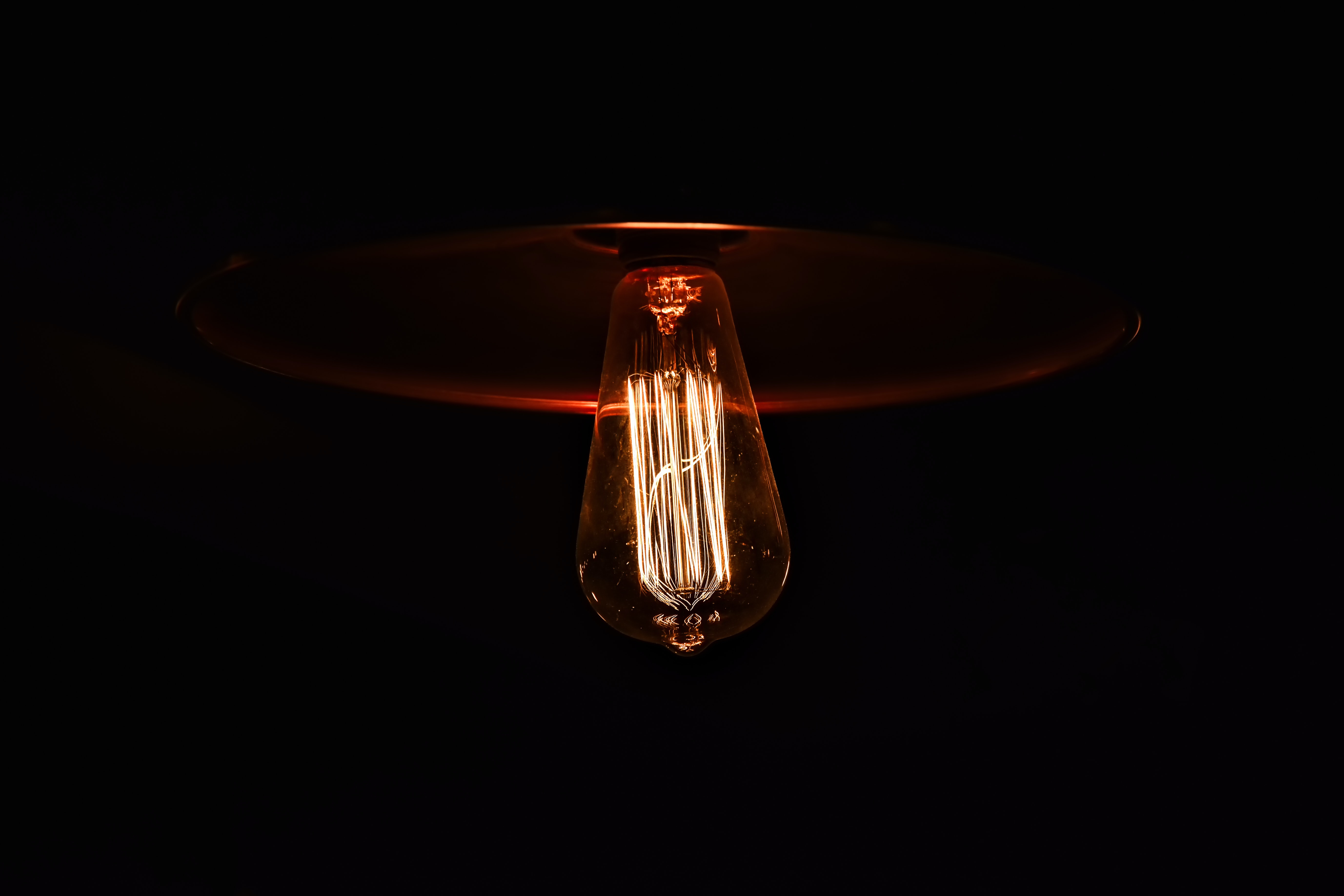 A faintly glowing light-bulb hanging from a ceiling in a dark room