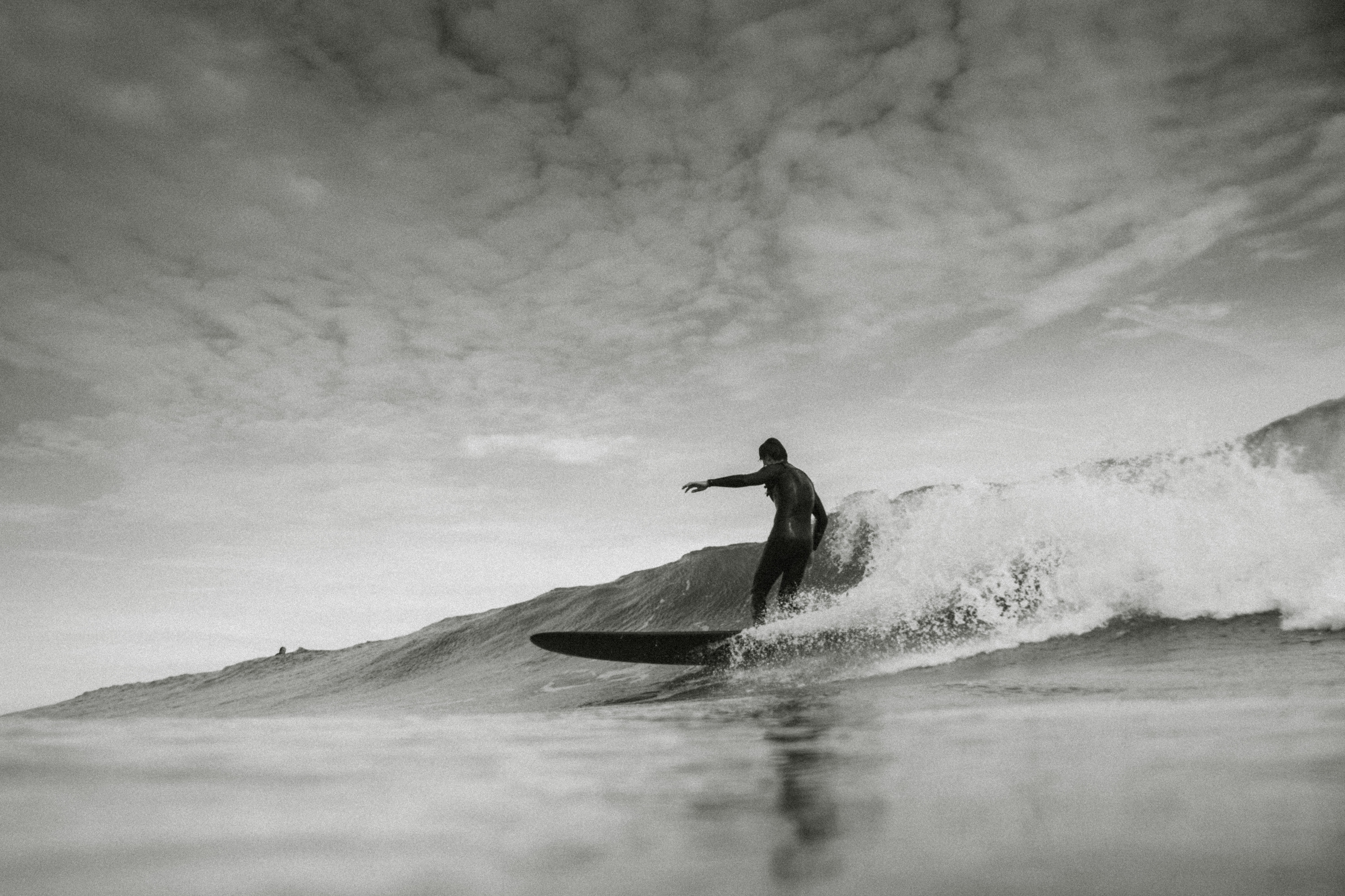 grayscale photo of person surfing under cloudy sky