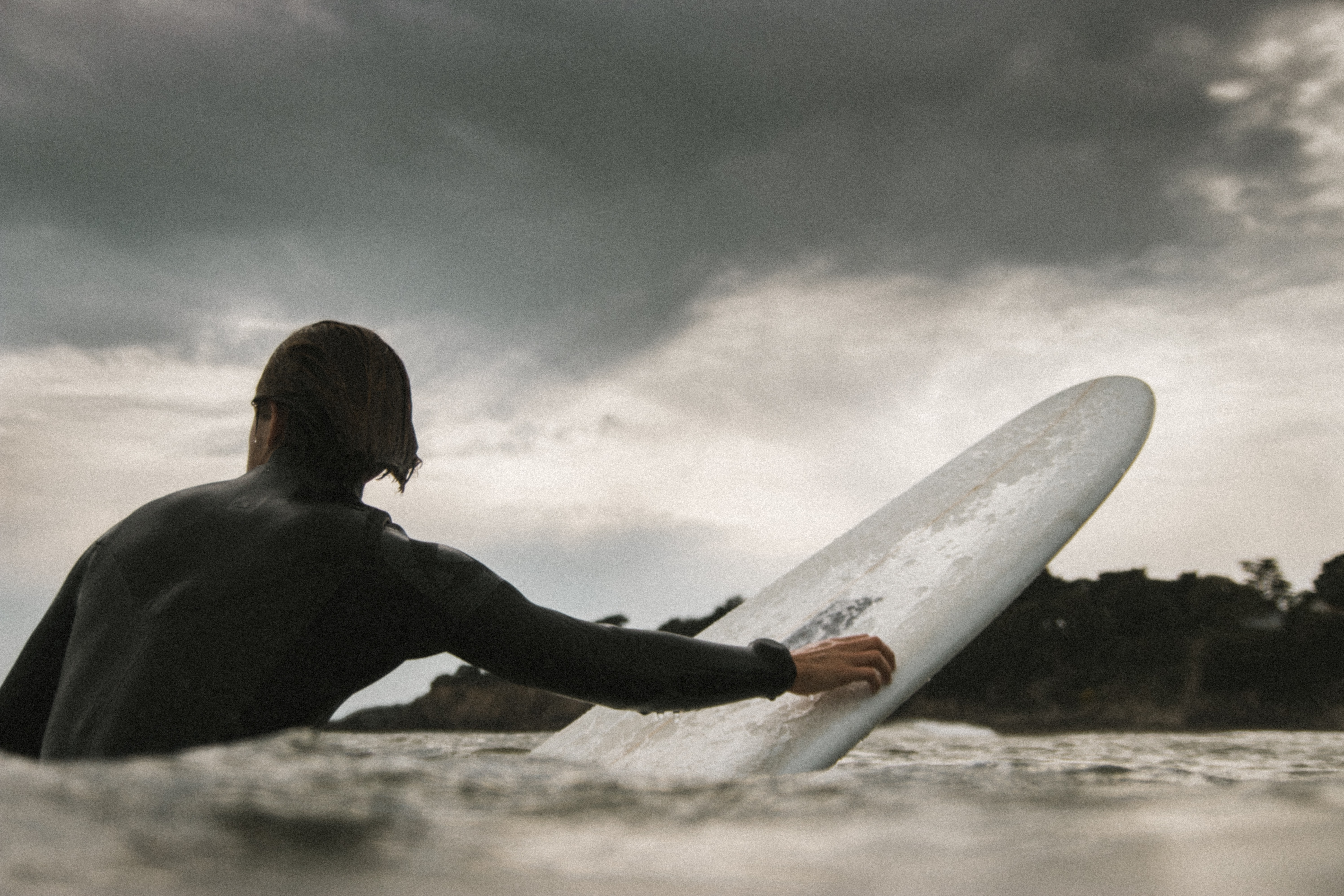 A black and white shot of a male surfer in the water, holding onto his surf board under a cloudy sky at Saint-Nazaire