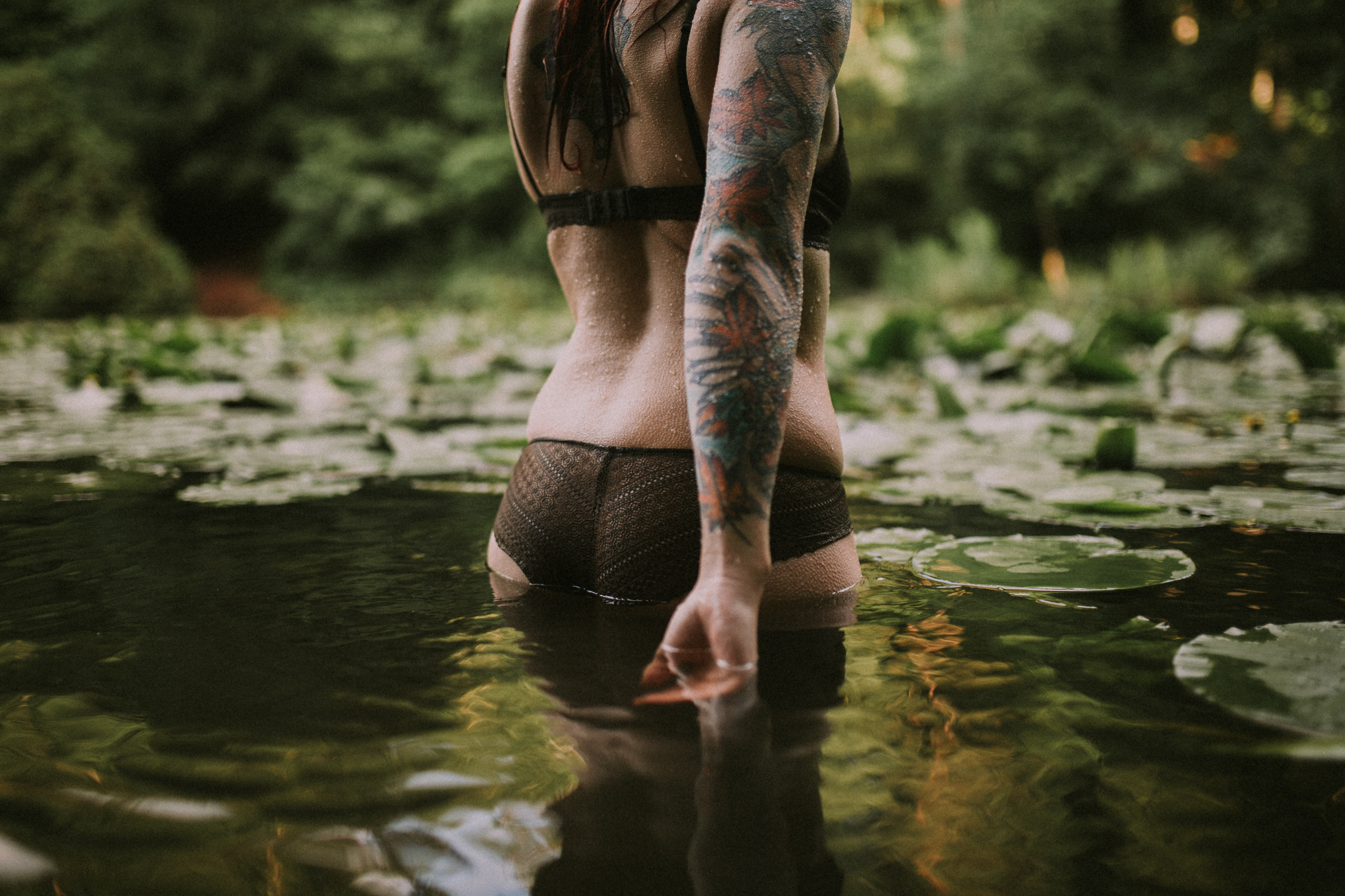 Woman with an arm sleeve tattoo wading in a pond
