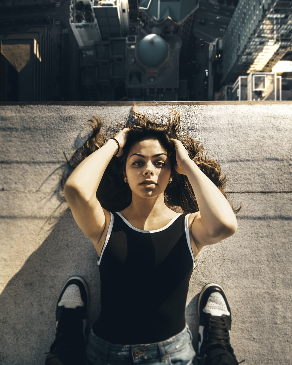 woman lying on gray flooring near buildings