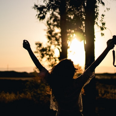 silhouette photo of woman raising her hands while holding DSLR camera