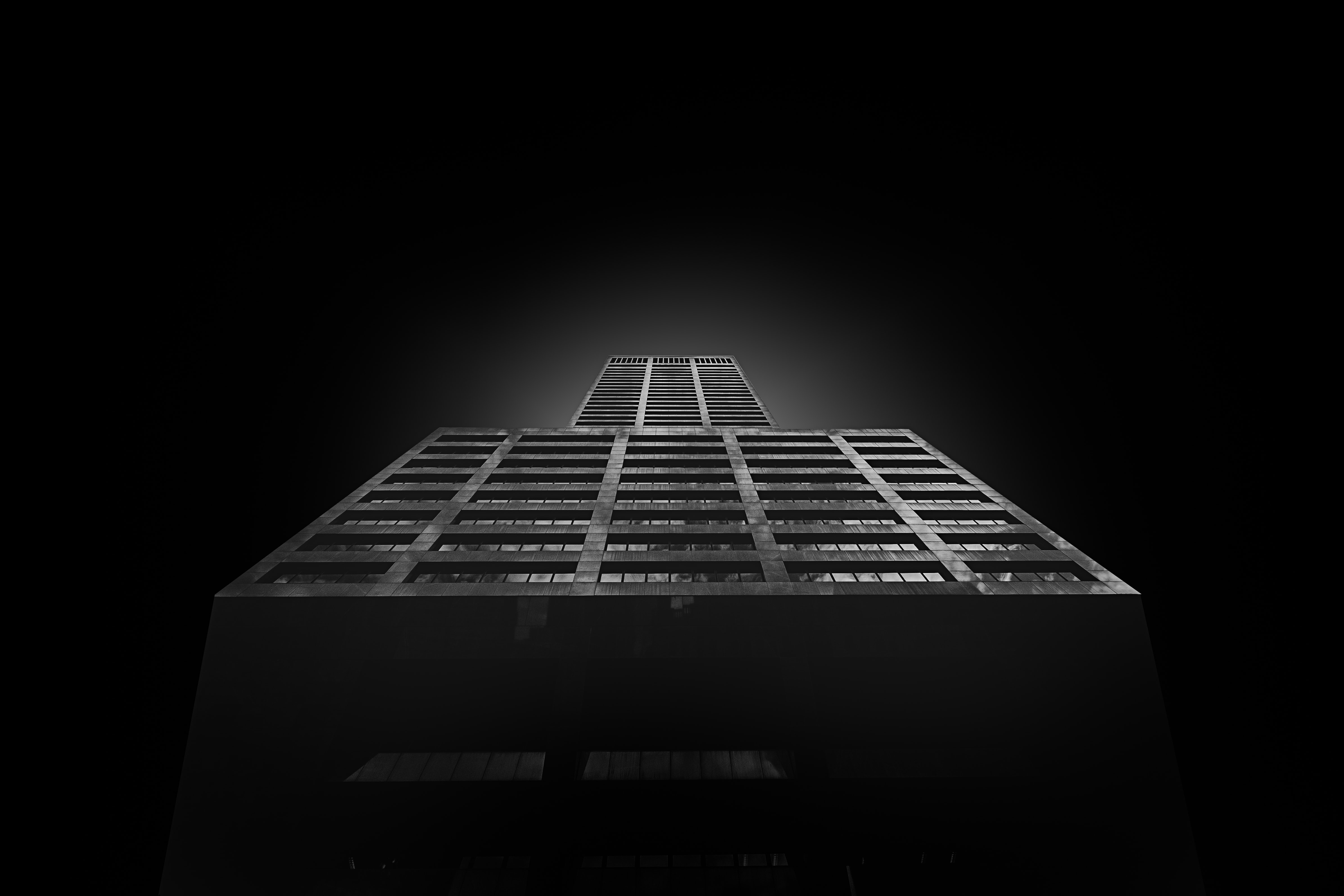 Black and white shot from below of building architecture and light glow on black background