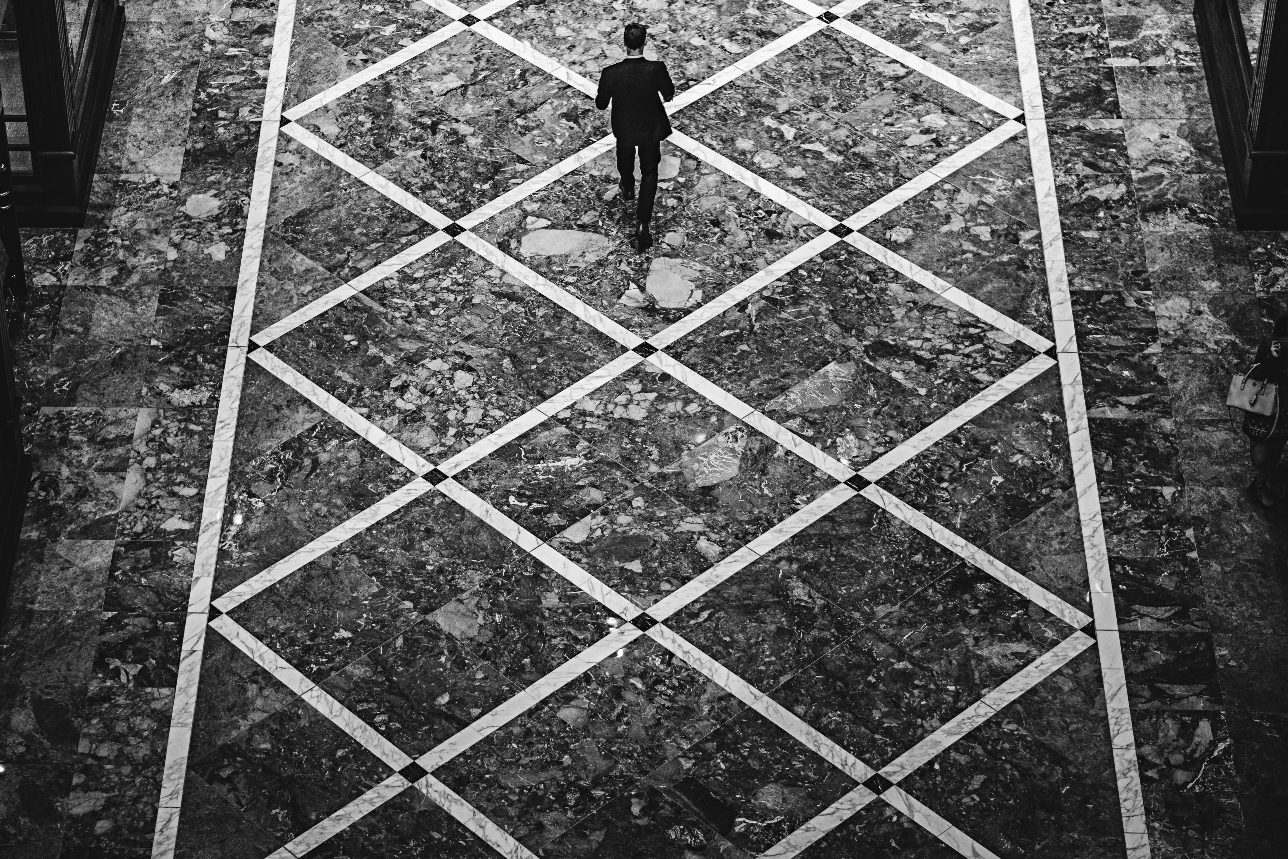 A male walking down a diamond-patterned street.