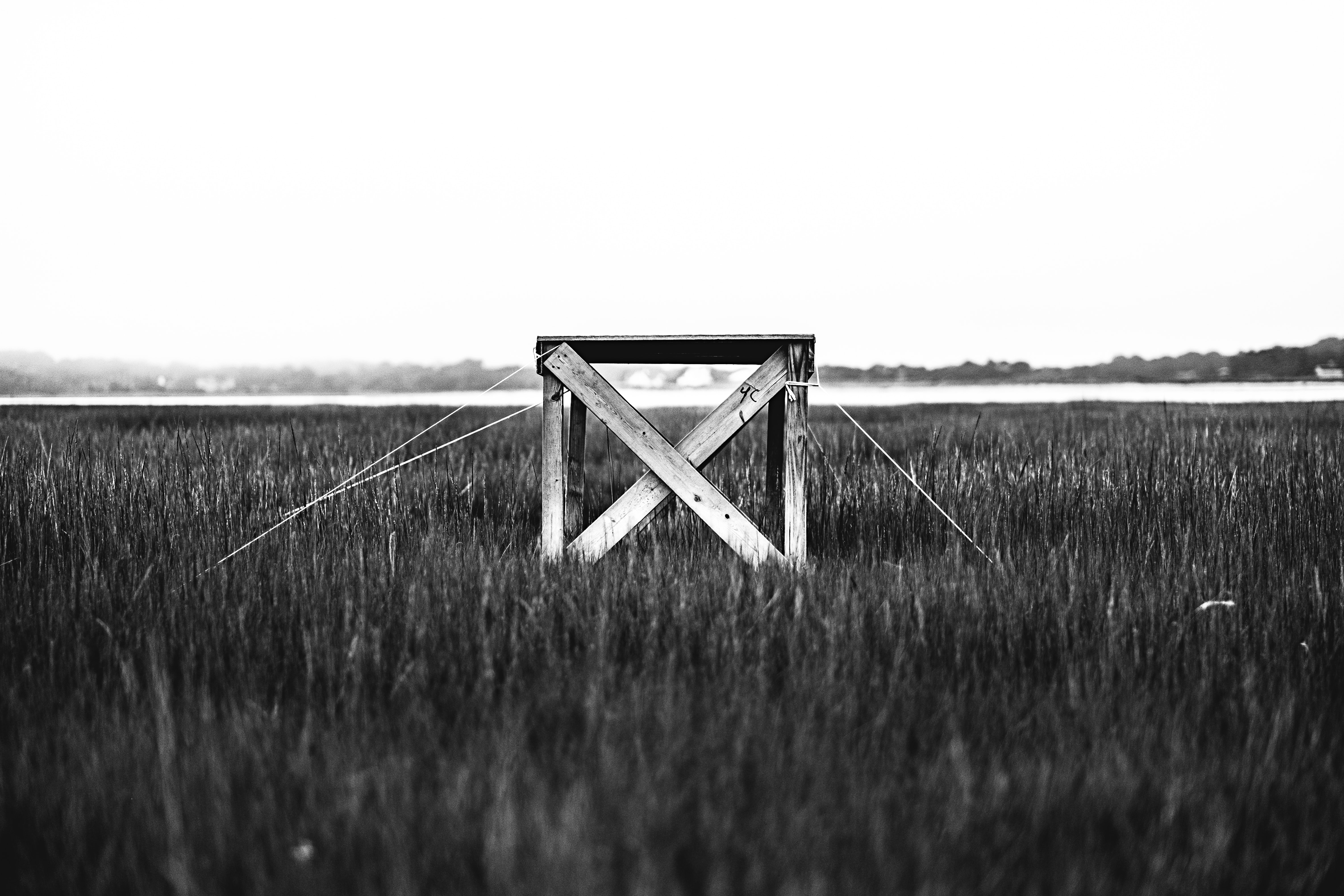 Black and white shot of wooden cube structure made of planks in field with clear sky