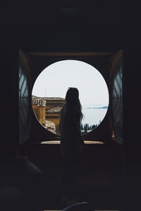 woman standing in front of round window