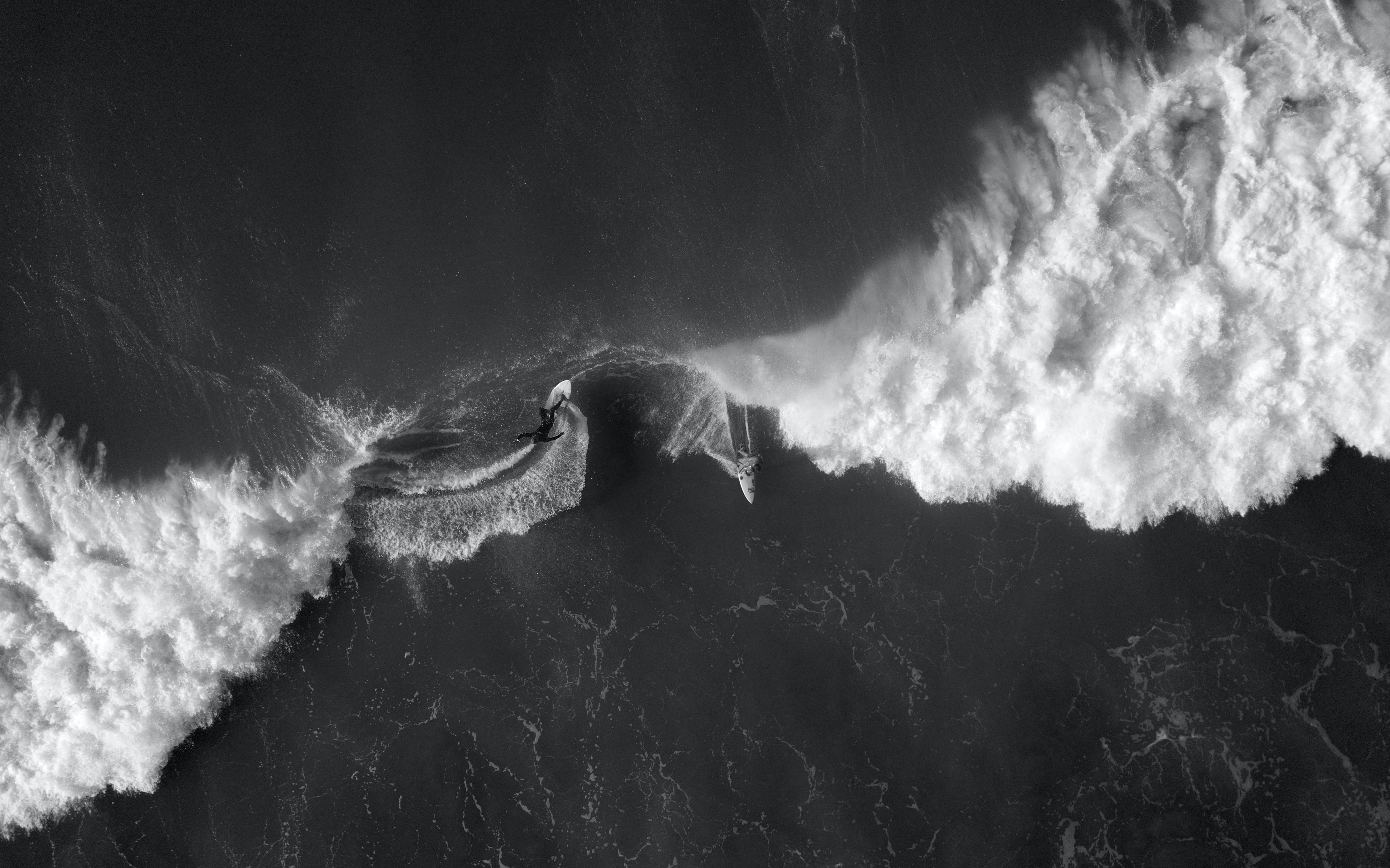 A black and white overhead drone shot of surfers riding foaming waves at Gisborne, New Zealand